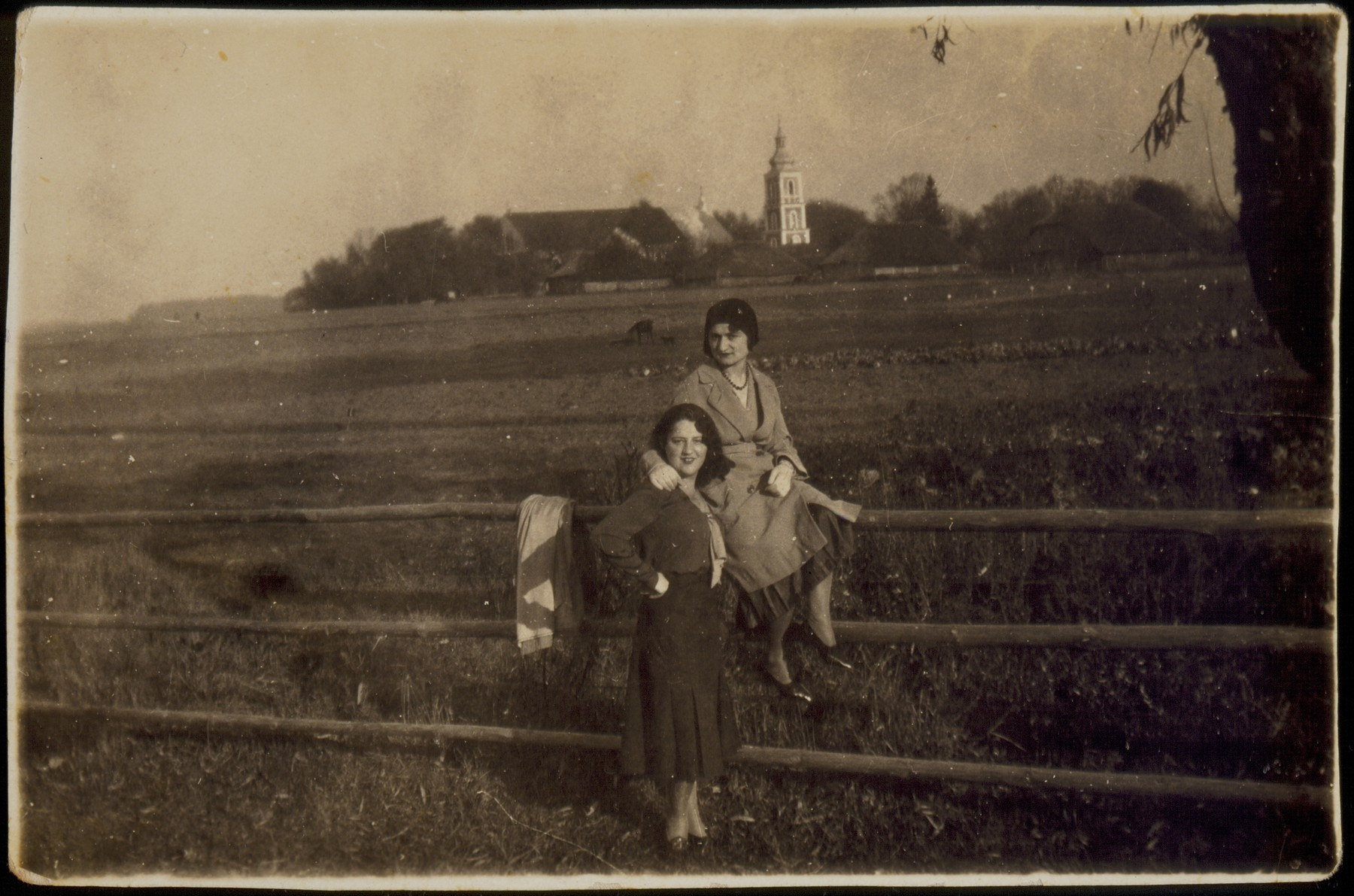 Two young women pose by a fence surrounding a Jewish-owned pasture.   Geneshe Kaganowicz is sitting, and Matle Sonenson is standing next to her.  The two best friends later became sisters-in-law after Geneshe married Matle's brother Leibke.  In the background is the Catholic church at Juryzdyki.