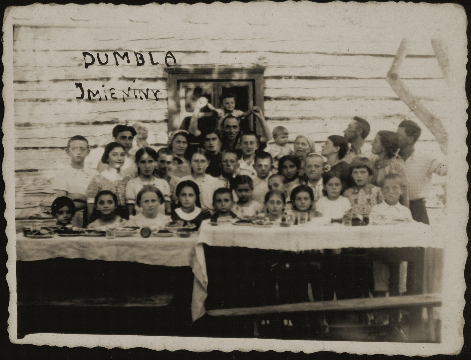 Children gather around a table in a summer camp in Dumbla.  Moshe Bastunski is standing on the far left.  In the center is Avigdor Katz and to his left is Benyamin (Niomke) Sonenson.  All the children and adults in the photo were murdered during the Holocaust.
