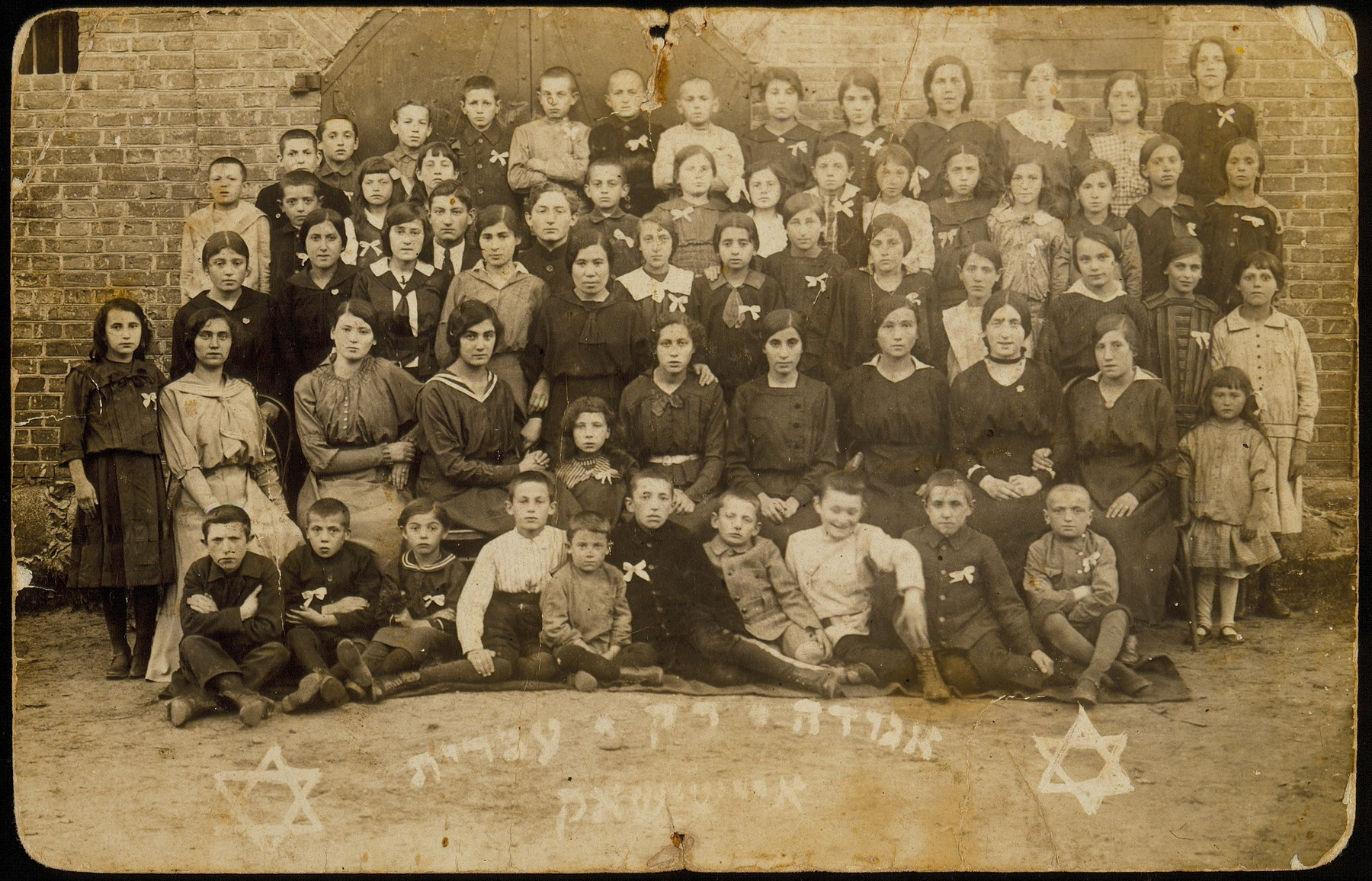 Members of the Rak Ivrit (Only Hebrew) society founded by Leah Wilansky.   The white bow on their chests indicates that Hebrew, not Yiddish, is the member's daily language.  In the third row, fifth from left, is Sarah Rubinstein, the Hebrew instructor, who was the first female teacher to teach boys as well as girls.    Shlomo Kiuchefski is sitting on the ground, fifth from right.  The little girl in the second row, far right, is Esther Katz.  Fourth row, standing to the right of Sarah Rubinstein, is Shaul Kaleko and his brother Simha; the boy directly behind Sarah is Moshe Sonenson.  Behind him in the last last row is his brother Shalom, wearing a black outfit.  A significant number of the people in the photo immigrated to Palestine or other various countries.