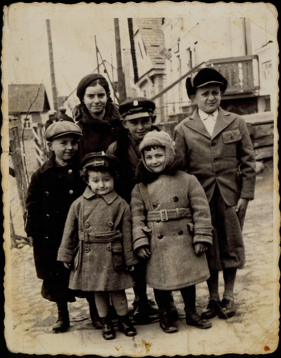 Benyamin Sonenson poses for a bar mitzvah portrait with his cousins only days before the massacre of Eisiskes' Jewish population.  Benyamin Sonenson's bar mitzvah in September 1941 was the last one to be celebrated in Eisiskes.  Standing near the house of Alte Katz are (right to left) Benyamin, Yitzhak Sonenson, Altke Tawlitski, and Hayyim Tawlitski.  Standing in the front are Meir Sonenson (right) and Oscar (Asher) Shereshefski.    Yitzhak survived in hiding, Oscar survived in Siberia; all the others were murdered by the Germans during the September 1941 mass shooting action in Eisiskes