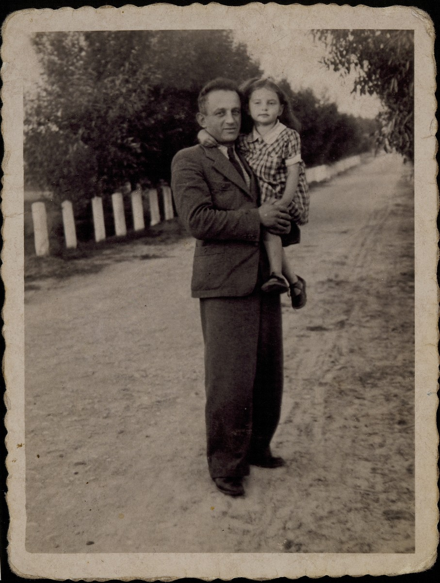 Moshe Sonenson holds his daughter Yaffa on the road leading to their summer cottage in Tetlance near Eisiskes.