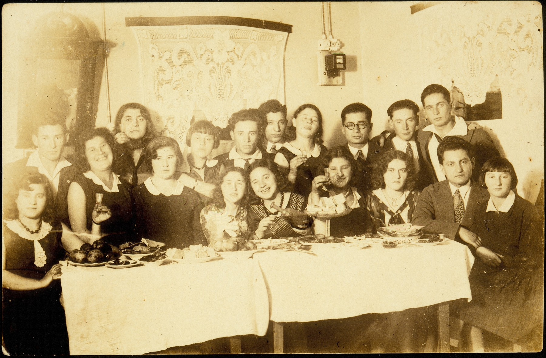 Young Jewish men and women pose around a table during a Saturday night party.    Pictured standing from right to left are: Dov Wilenski, Shmuel Berkowicz, Avraham Politacki, unknown, Muni Zahavi, Motke Burstein, unknown and Rina Lewinson.  Sitting from right to left are: Esther Katz, Simha Kaleko, Flora Kagan, unknown, unknown, unknown, unknown, Miriam Koppelman, unknown, unknown.  Those who survived the war include Shmuel Berkowicz, Dov Wilenski, and Rina Lewinson who immigrated to Palestine, and Esther Katz, who immigrated to Colombia. Flora Kagan immigrated to the United States.