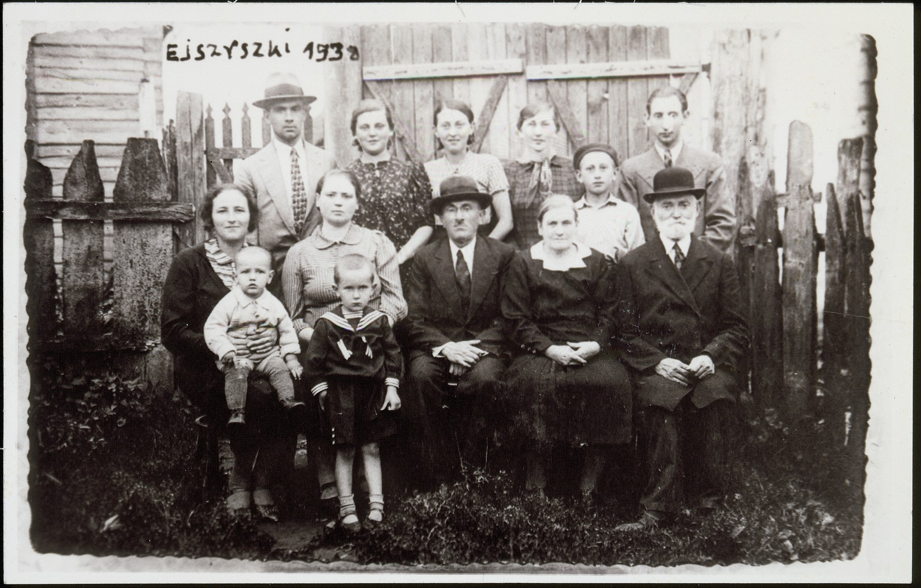 A family photo in honor of the emigration of Gittele Rabinowitz.    Standing (right to left) Moshe-David Katz, his mother Alte (the Shtetl photographer and pharmacist), his sister Shoshana, Gittele Rabinowitz, and Ephraim Karnefski. Seated (right to left) Yankel Resnik, his wife, Yitzhak and Hayya Rabinowitz, Taibl Karnefski nee Resnik, and the two Karnefski sons, Moshe and Zissel, the grandsons of Yaakov Resnik. With the exception of Gittele everybody ele was murdered during the Holocaust.