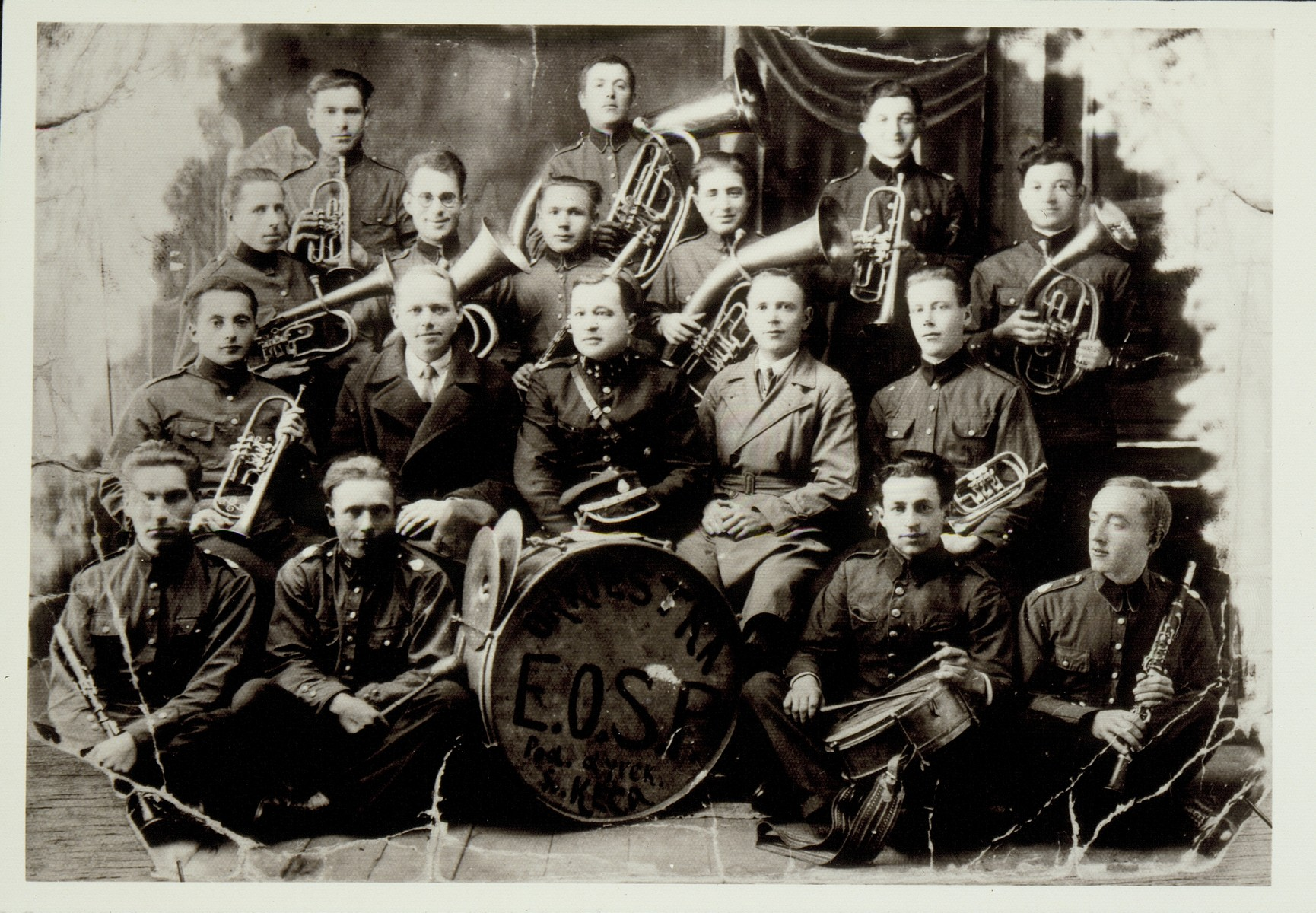 Group portrait of members of the Eisiskes fire department orchestra, which included both Poles and Jews.    Among the Jews pictured are: Bere-Leibke Garmenishki, Shepske Sonenson and Motl Narodowicz (top row, right to left); Menahem Politacki (third row from the front, second from the left, wearing glasses), and Eishke Levin (second row from the front, far left). The Polish conductor Gotowicky, is seated behind the drum.  Menahem Politacki immigrated to Palestine before the war; Motl Narodowicz survived the war as a partisan.