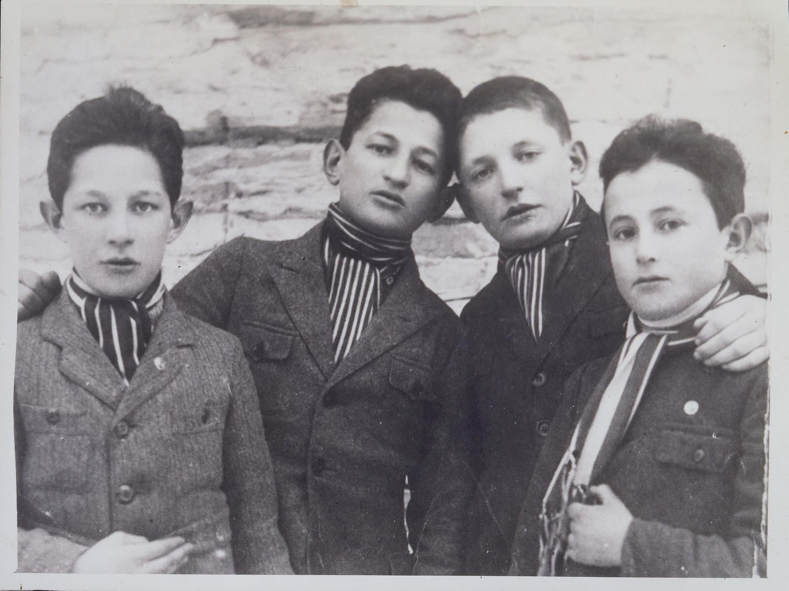 Four Jewish teenage boys from Eisiskes pose wearing striped cravats.  Pictured from right to left are: Velvke Saltz, Motke Kiuchefski, Leibke Sonenson and Israel Szczuczynski.  Velvke Saltzs immigrated to the United States; Motke Kiuchefski fled to the Soviet Union; Leibke Sonenson was killed by the Germans in the September 1941 mass shooting action in Eisiskes; and Israel Szczuczynski was killed by members of the Polish Home Army.