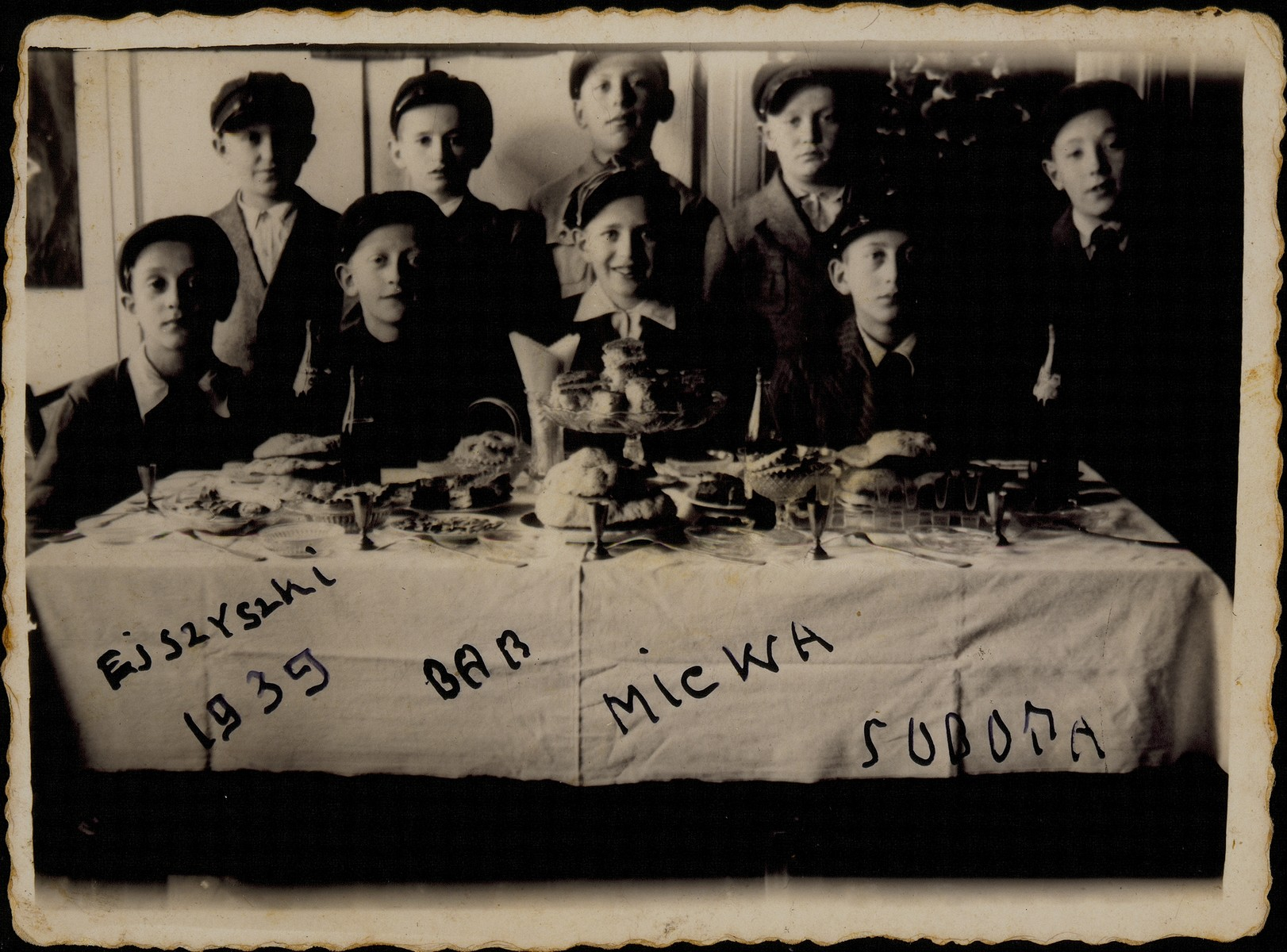 Group portrait of Jewish children attending the Bar Mitzvah party of Avremele Botwinik in Eisiskes.  Among those pictured are Avremele Botwinik (seated behind the cake), Moshe Bastunski (seated second from the left), Avigdor Katz (seated on the right), Moshe Kaplan (standing second from the right), Elisha Koppelman (standing second from the left).  Only the Bar Mitzvah boy survived the war (as a partisan).  Elisha Koppelman was killed by members of the Polish Home Army.  The others were killed by the Germans during the September 1941 mass shooting action in Eisiskes.
