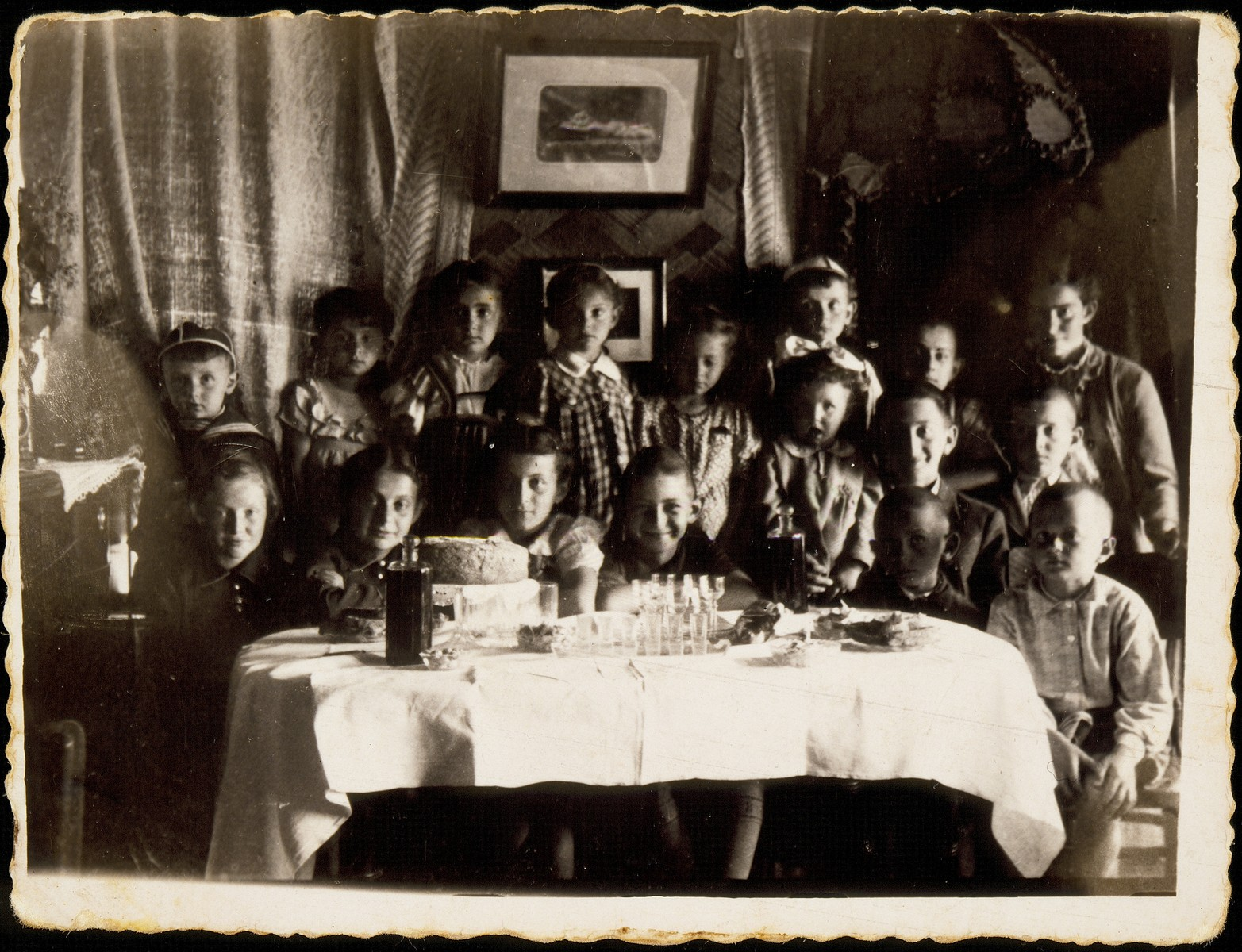 Children gather around a table at an end of the school party, in honor of Yitzhak Sonenson.  The party took place in the Sonenson's living room only days before the German invasion.    Sitting in the center is Yitzhak Sonenson.  Second from right is Meir (Mulke) Sonenson sitting on the lap of Avigdor Katz.  Second from left is Gittele Sonenson and at the far left is Hayya Tawlitski. Standing at the extreme right is Altke Tawlitski.  Yaffa Sonenson is in the checkered dress, and on her right is Shirale Kaganov.    All the children were murdered during the Holocaust except for Gittele Sonenson who died from TB in the cave where she was hiding, and Yitzhak and Yaffa Sonenson survived the Holocaust in hiding. The house was totally destroyed when the local population looked for hidden loot.