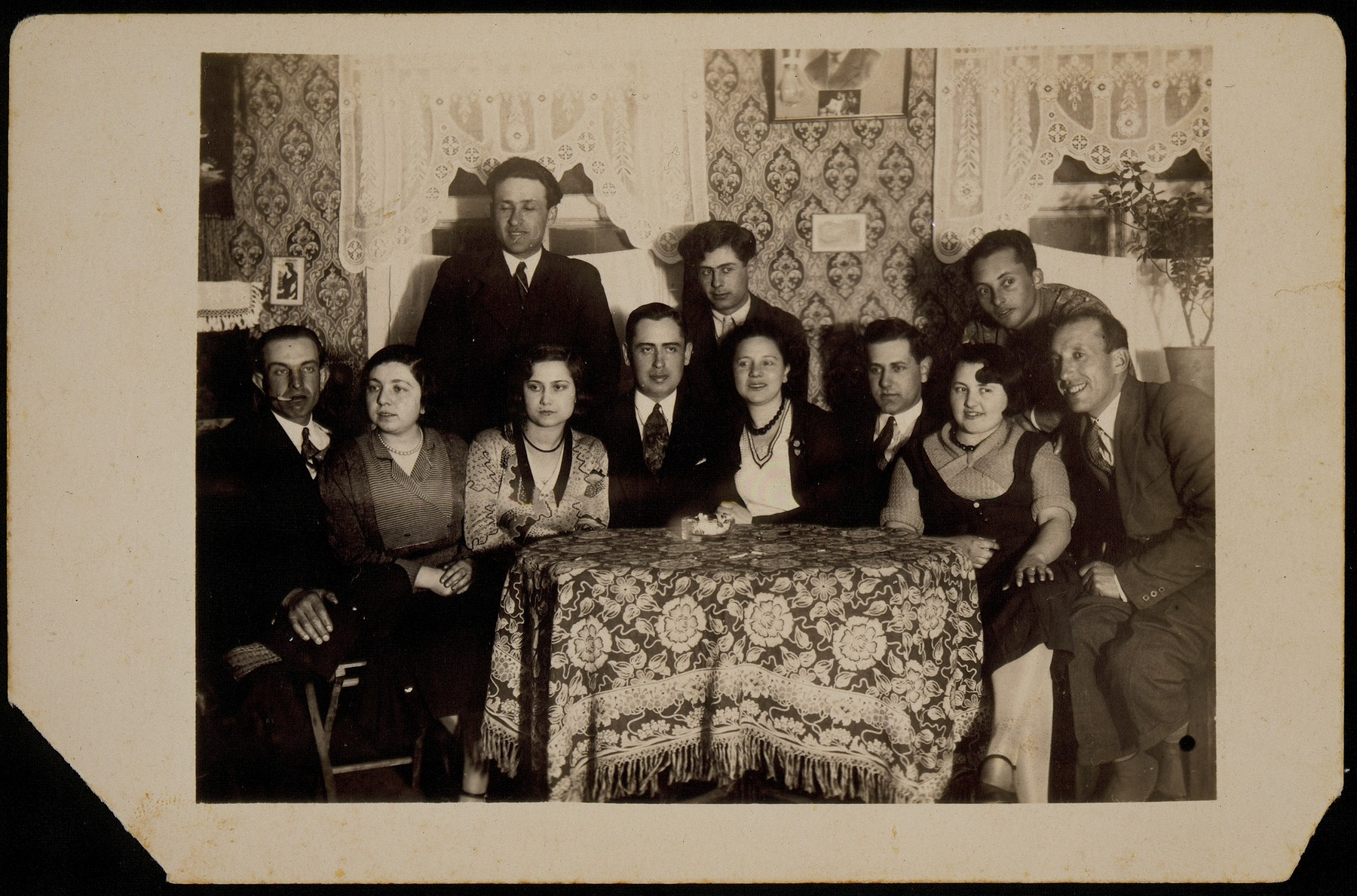 A group of young Jewish men and women sit around a table during a Saturday night party in Eisiskes.  Among those pictured are Eishke Levine (second from the right), Shaul Dubrowicz (sitting in the middle), Motke Kaganowicz (standing on the left) and Shlomo Kiuchefski (sitting on the left).  Most of those pictured were killed during the Holocaust.