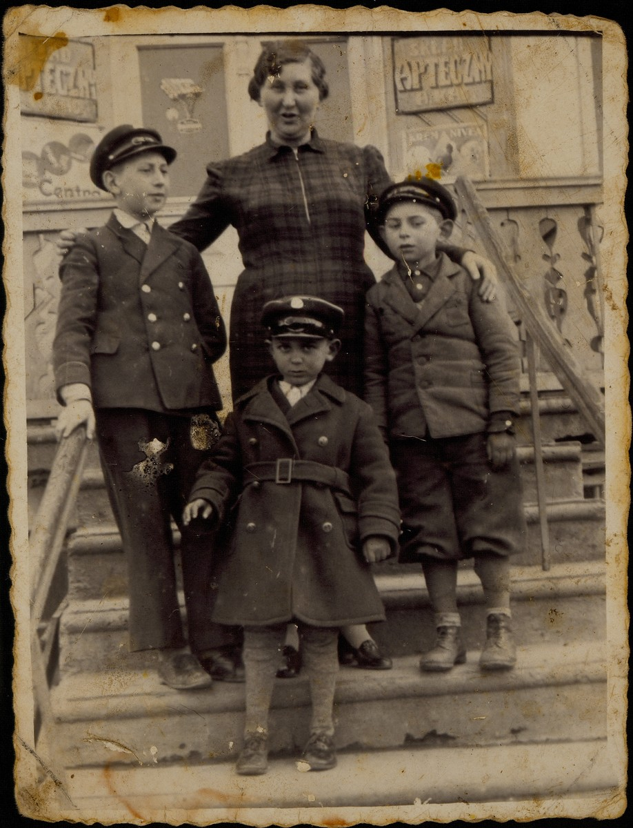 Alte Katz stands on the steps of her drugstore flanked by three young relatives.   Alte Katz is in the center. To her right is her youngest son Avigdor.  To her left is her oldest grandson Yitzhak Sonenson.  In front of her is one of her great nephews Shaul Replianski, the son of Esther (nee Dwilanski) and Mordekhai Replianski. Shaul was the grandson of Shmuel Dwilanski.   Alte Katz, her son Avigdor, and Shaul were murdered by the Germans during the September 1941 mass shooting action in Eisiskes.  Yitzhak survived the Holocaust in hiding.