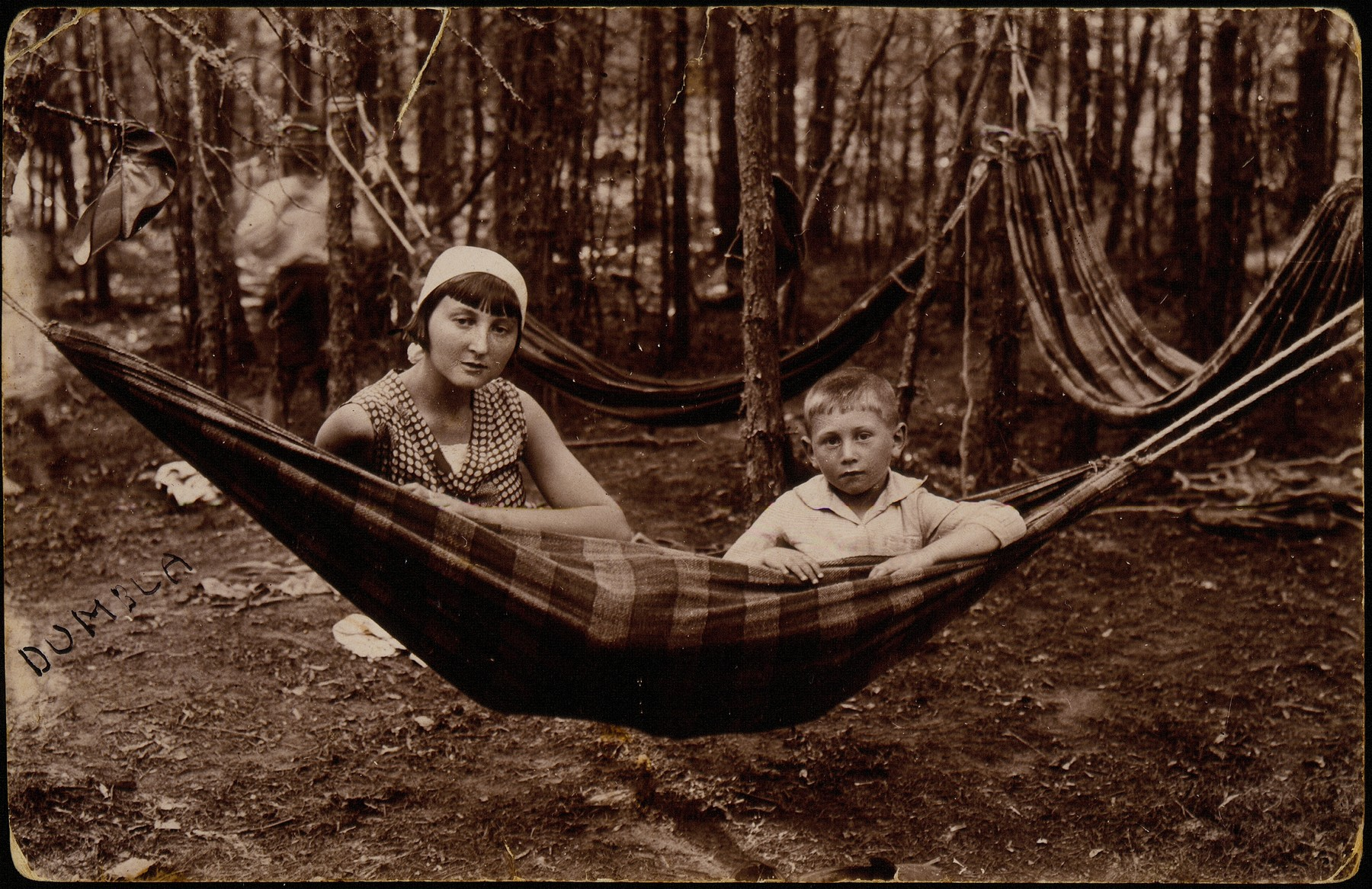 A Jewish brother and sister sit in a hammock while vacationing in Dumbla, a summer resort in Eisiskes.  Pictured are Esther Katz (later Resnik) and her brother Hayyim.