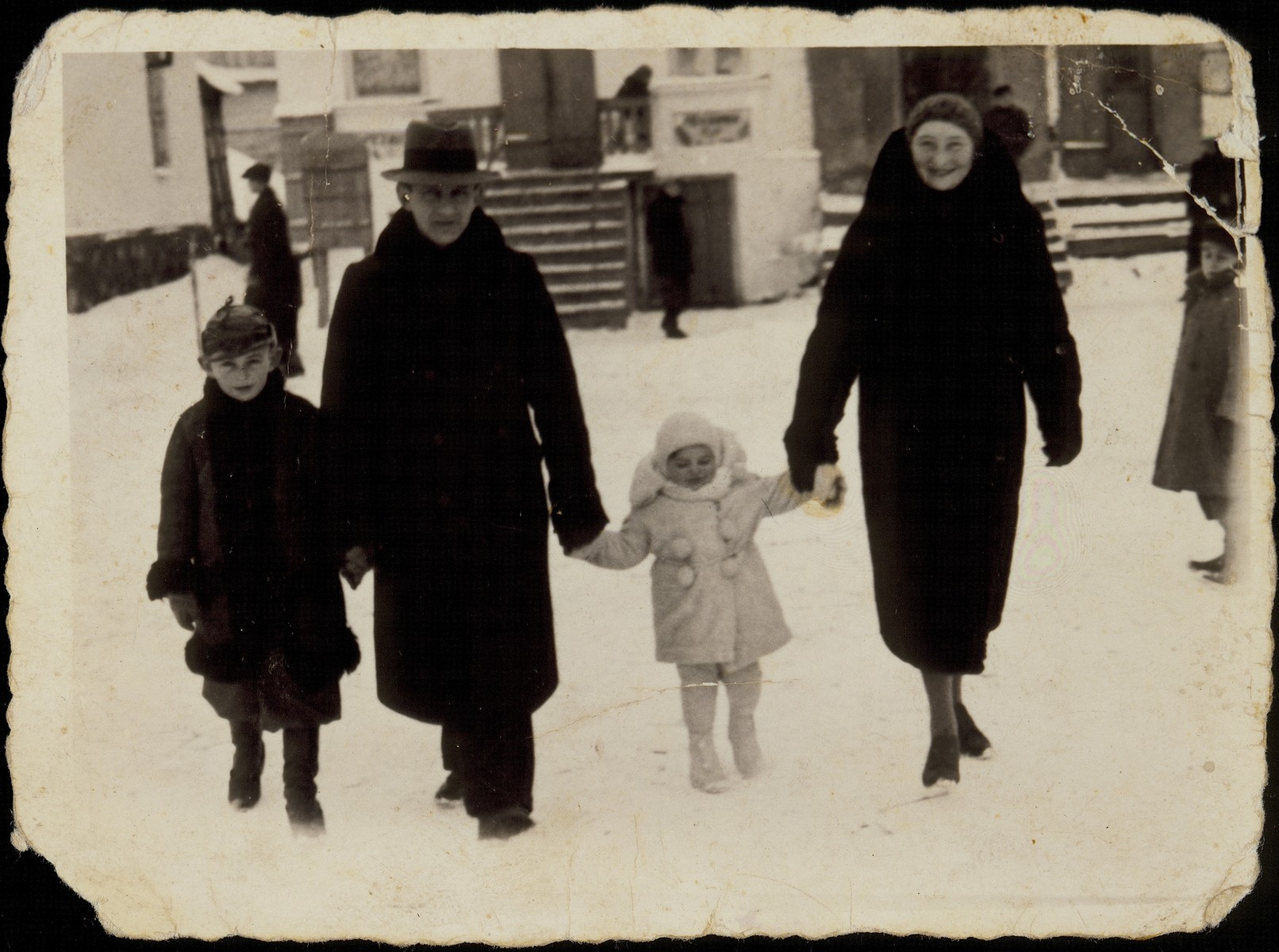 The Sonenson family walks along a snow-covered street in Eisiskes.  Pictured are Moshe and Zipporah Sonenson with their children, Yitzhak and Yaffa.