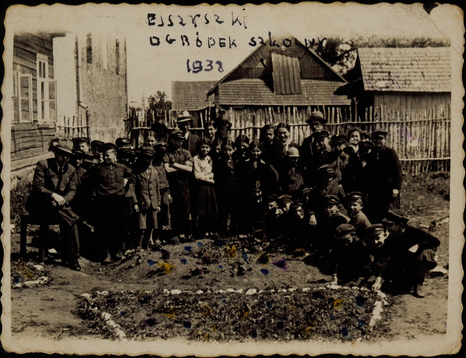 Children from the Hebrew School work in the school's garden in preparation for immigration to Palestine.  Supervising them are three of their teachers: Okun, Shael Michalowski, and a teacher from the city of Belski. Most of the children and teachers were murdered during the Holocaust.