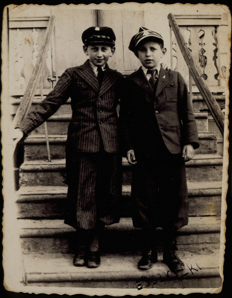 In honor of their bar mitzvah, two best friends, Avigdor Katz (left) and Avremele Botwinik, pose for a photo on the steps leading to Avigdor's house which also served as the pharmacy and photo studio of his mother Alte Katz.