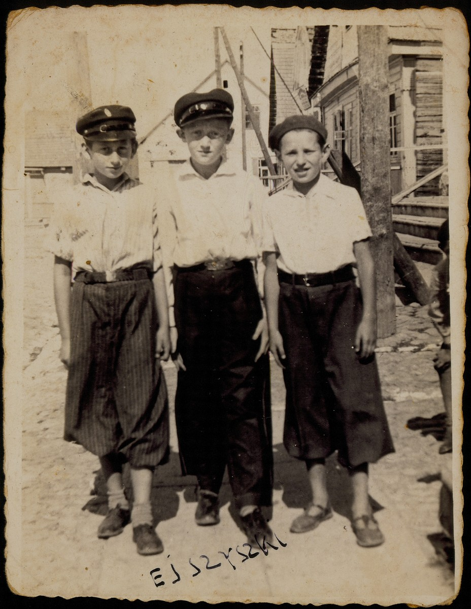 Three best friends stand in the market square near the house of Alte Katz.  (left to right): Avigdor Katz, Moshe Bastunski, and Avraham Botwinik.  Avigdor and Moshe were murdered by the Germans during the September 1941 mass shooting action. Avraham survived as a partisan and emigrated to the United States.