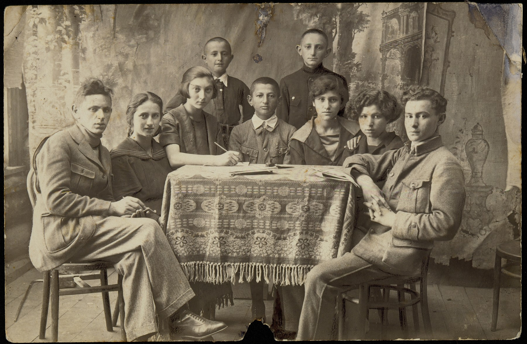 Board members of the Brenner Zionist Club and Jewish National Fund (Keren Kayemet) in Eisiskes, pose around a table.    Among those pictured are: Peretz Kaleko (sitting at the far right), Leah Koppelman (sitting third from the right), Leibke Sonenson (sitting fourth from the right), and club secretary, Zipporah (Katz) Sonenson (fifth from the right). Peretz Kaleko and his wife Leah Koppelman immigrated to Palestine before the war.  Leibke Sonenson was killed by the Germans in the September 1941 mass shooting action in Eisiskes.