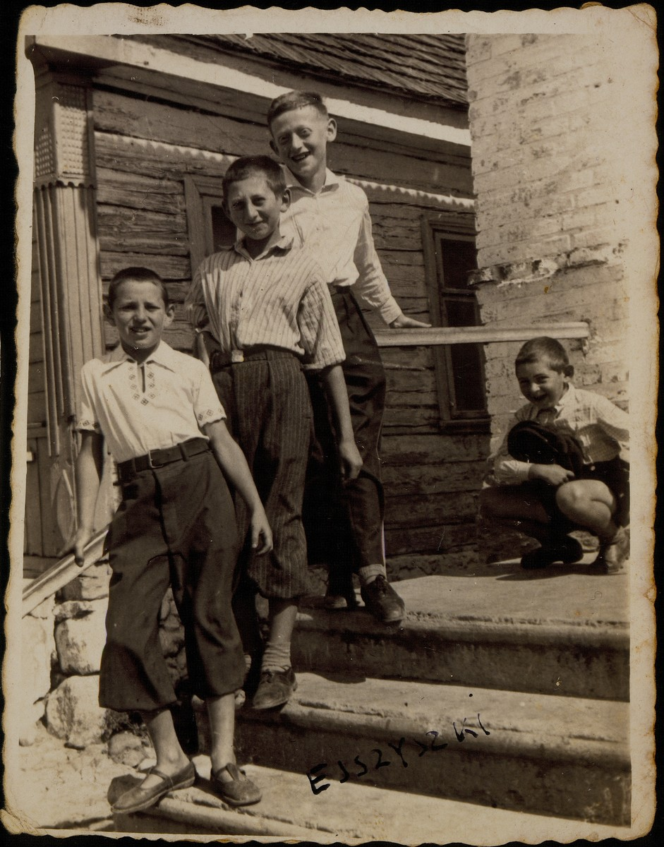 Three boys pose on the steps of the Botwinik house.  (front to back): Avraham Botwinik, Avigdor Katz, and Moshe Bastunski. Sitting in the back is Yitzhak Sonenson.   Moshe and Avigdor were murdered by the Germans during the September 1941 mass shooting action in Eisiskes; Avraham immigrated to America, and Yitzhak immigrated to Israel.