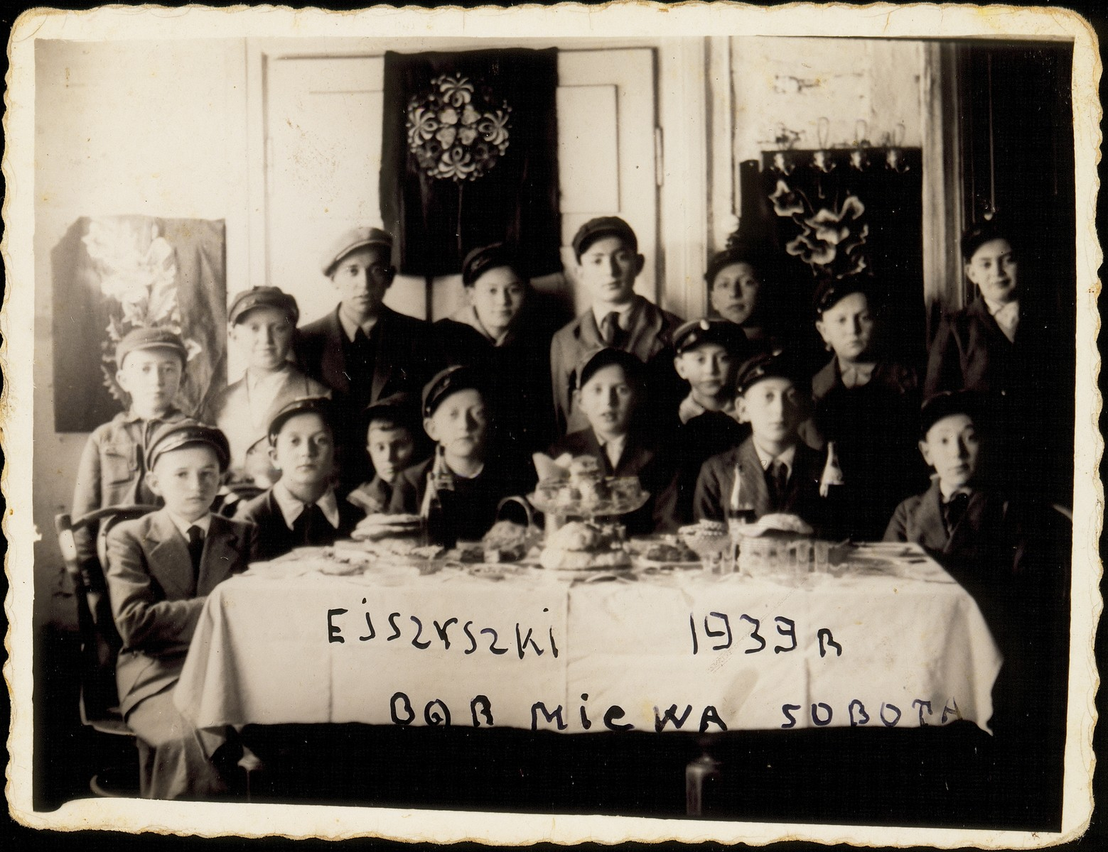 Group portrait of Jewish children attending the Bar Mitzvah party of Avremele Botwinik in Eisiskes.  Among those pictured are Avremele Botwinik (seated behind the cake), Moshe Bastunski (seated fourth from the right, next to Avremele), Avigdor Katz (seated second from the right), Elisha Koppelman (first on the left), Hillel Botwinik (a brother, standing third from the left), Yitzhak Botwinik (a brother, standing fifth from the left).  Only the Bar Mitzvah boy survived the war (as a partisan).  Elisha Koppelman was killed by members of the Polish Home Army.  The others were killed by the Germans during the September 1941 mass shooting action in Eisiskes.