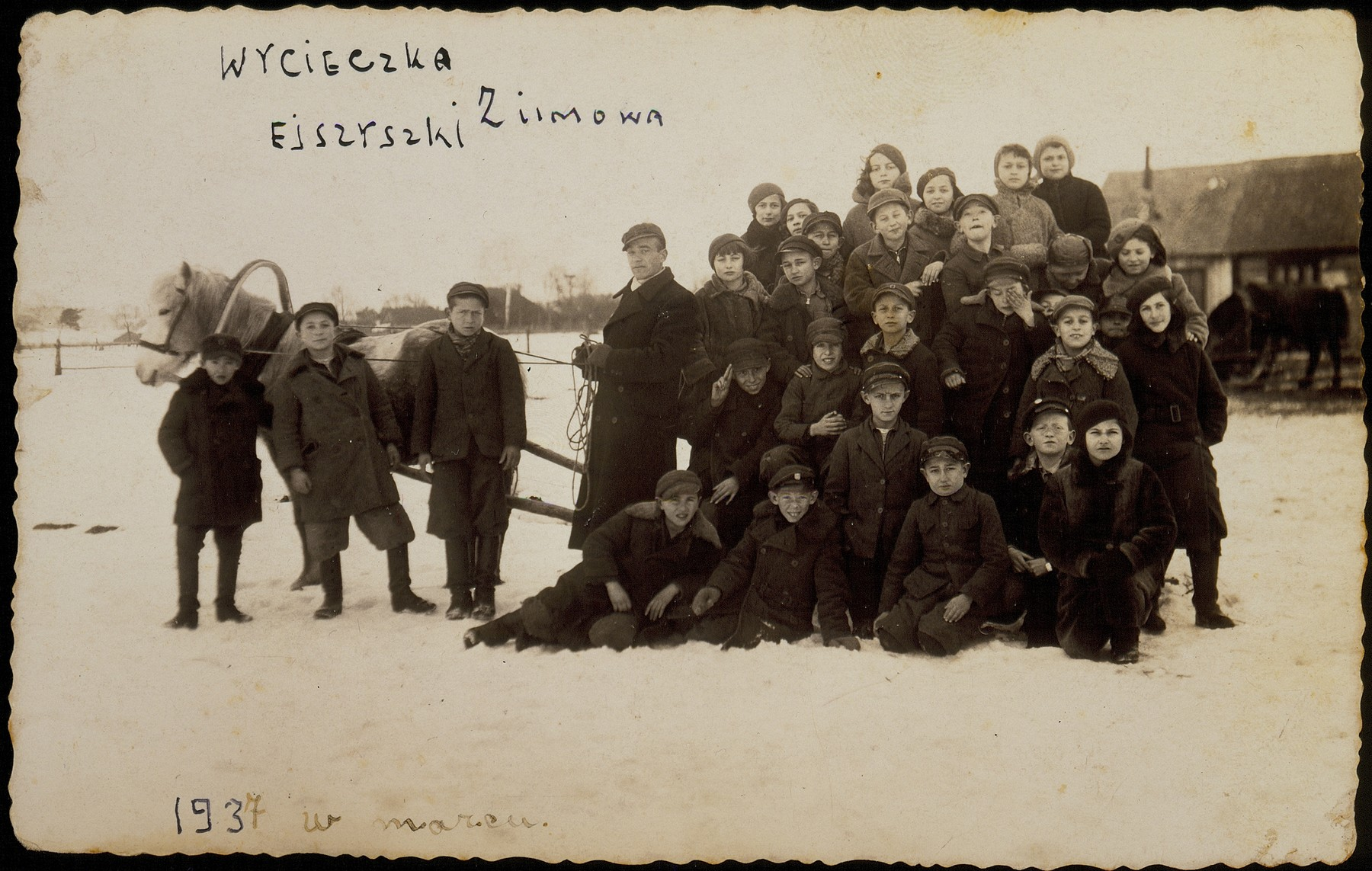 A school class gathers by a horse-drawn sleigh during a winter nature trip to the countryside.  Only three boys survived the Holocaust as teenage partisans:  Layzer Balon (sitting in the snow, left, next to the teacher's feet);  Moshe Edelstein (standing, third from left); and Reuven Paikowski (top row, third from left, biting his lips). The teacher, Leibke Botwinik was severely wounded by the Polish Home Army. Hirshke Mendelowitch (front row, fourth from right) was also a victim of the Polish Home Army. All the others were murdered  in the September 1941 massacre in Eisiskes.