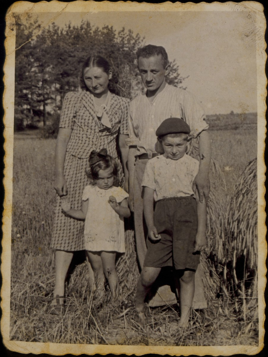 Moshe Sonenson poses with his wife and children in a field they once owned.  Pictured are Moshe and Zipporah Sonenson and their children Yaffa and Yitzhak Uri.