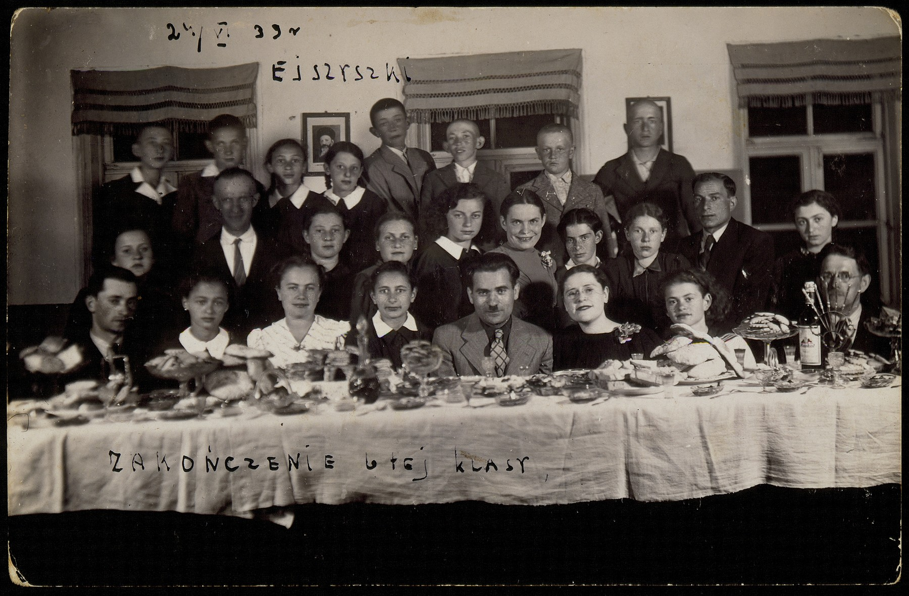 Students from the Hebrew School in Eisiskes celebrate their graduation.  Sitting second from left is Leilke Shesko.  Fourth from left is Sheine Dwilanski. Most of those pictured were murdered during the Holocaust.