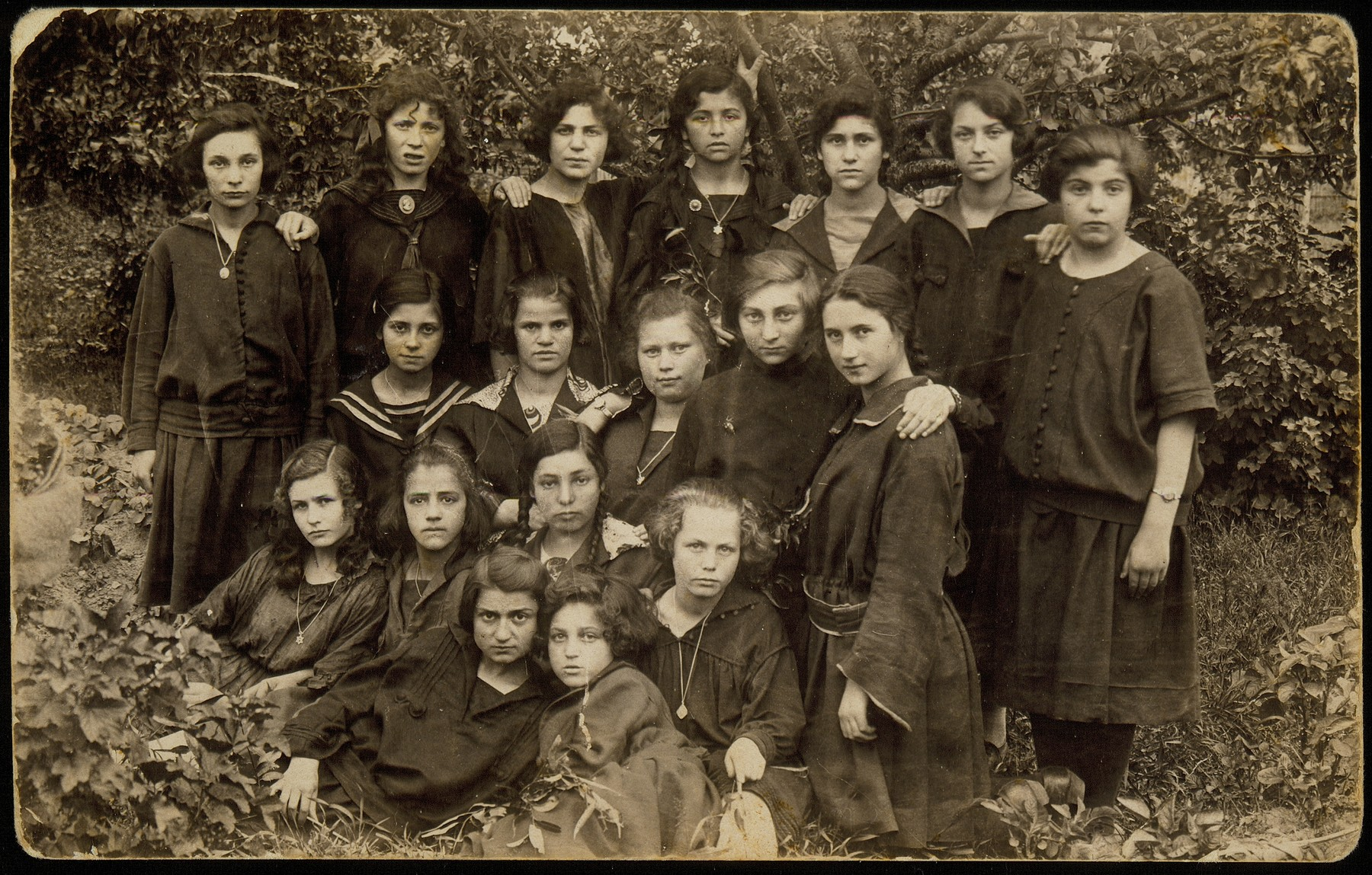 Group portrait of teenage girls beloning to a social group known as the 21 Club.   In 1921, twenty-one teenage girls, all Hebrew students established an apolitical friendship society and named it  Club 21.  Their younger sisters decided to establish a similar club, simply named Our Circle.  Many of these young women emigrated or moved to larger towns during the 1930s.   Among the Club 21 members: Mattle Sonenson (front right) and her best friend Geneshe Kaganowicz; Zipporah Katz (third row, second from right);  Leah Koppelman (top row, fourth from right).