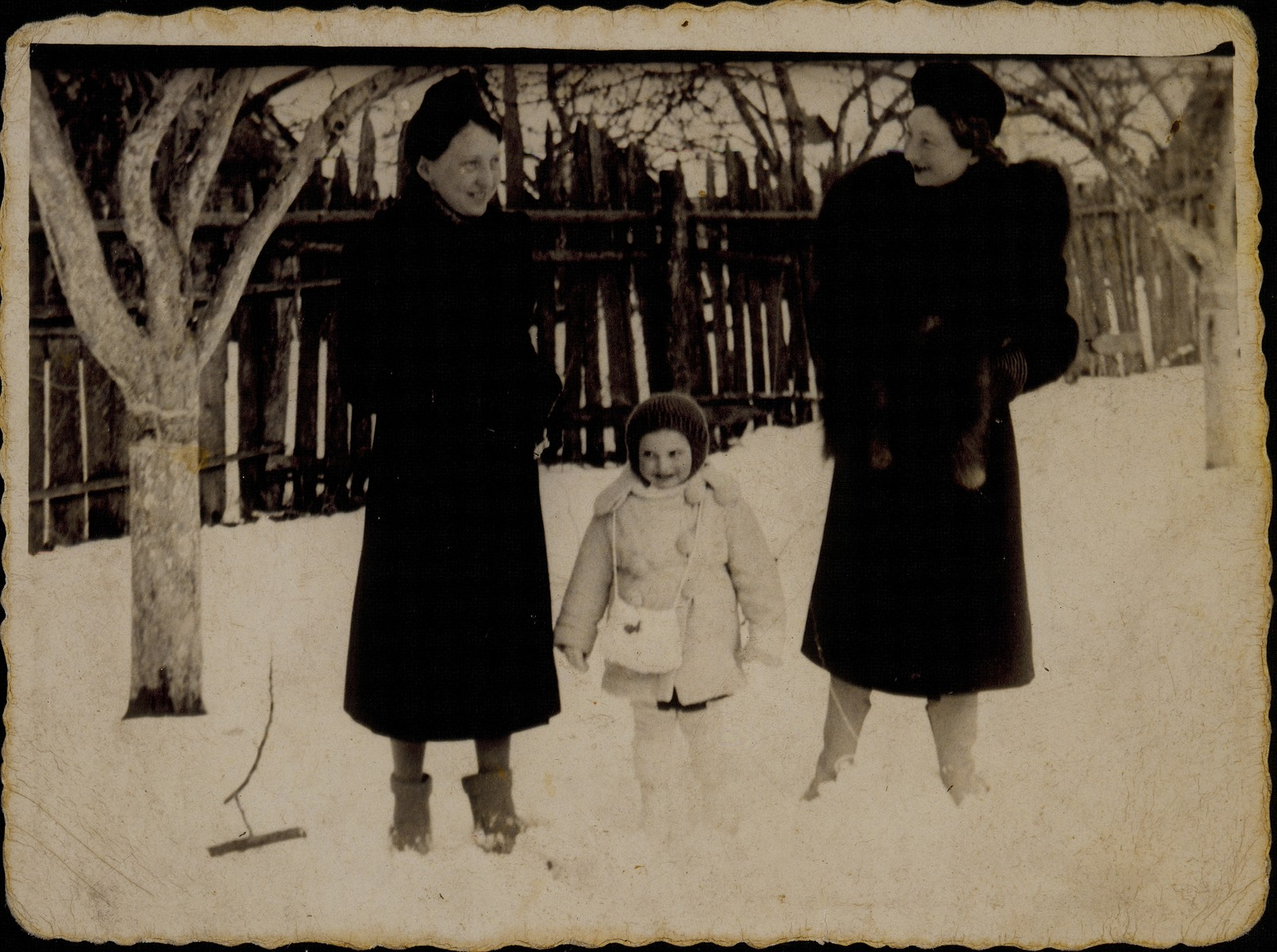 A young Jewish girl poses in the snow between her mother and her aunt.  Pictured are Yaffa Sonenson (center) with her mother, Zipporah (Katz) Sonenson (right) and her aunt, Shoshana Katz (left).