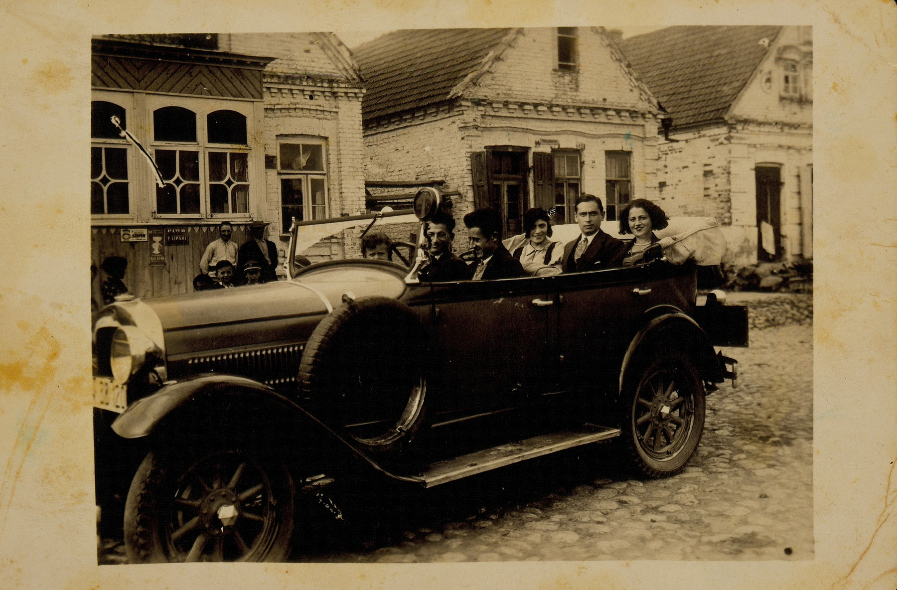 A visitor to Eisiskes takes his friends for a car ride in the early 1930s.   Seated next to the driver is Leibke Sonenson and his nephew Benyamin.  In the back seat (left to right) are Matle Sonenson Shereshefski, Shaul Dubrowicz and the driver's friend.  The little boy without the hat on the extreme left is Leibke Kaganowicz (Leon Kahn).  The houses in the background belong to the Kaganowicz and Blacharowicz families.  Matle survived the war in Siberia; all the others, except for Leon, perished during the Holocaust.