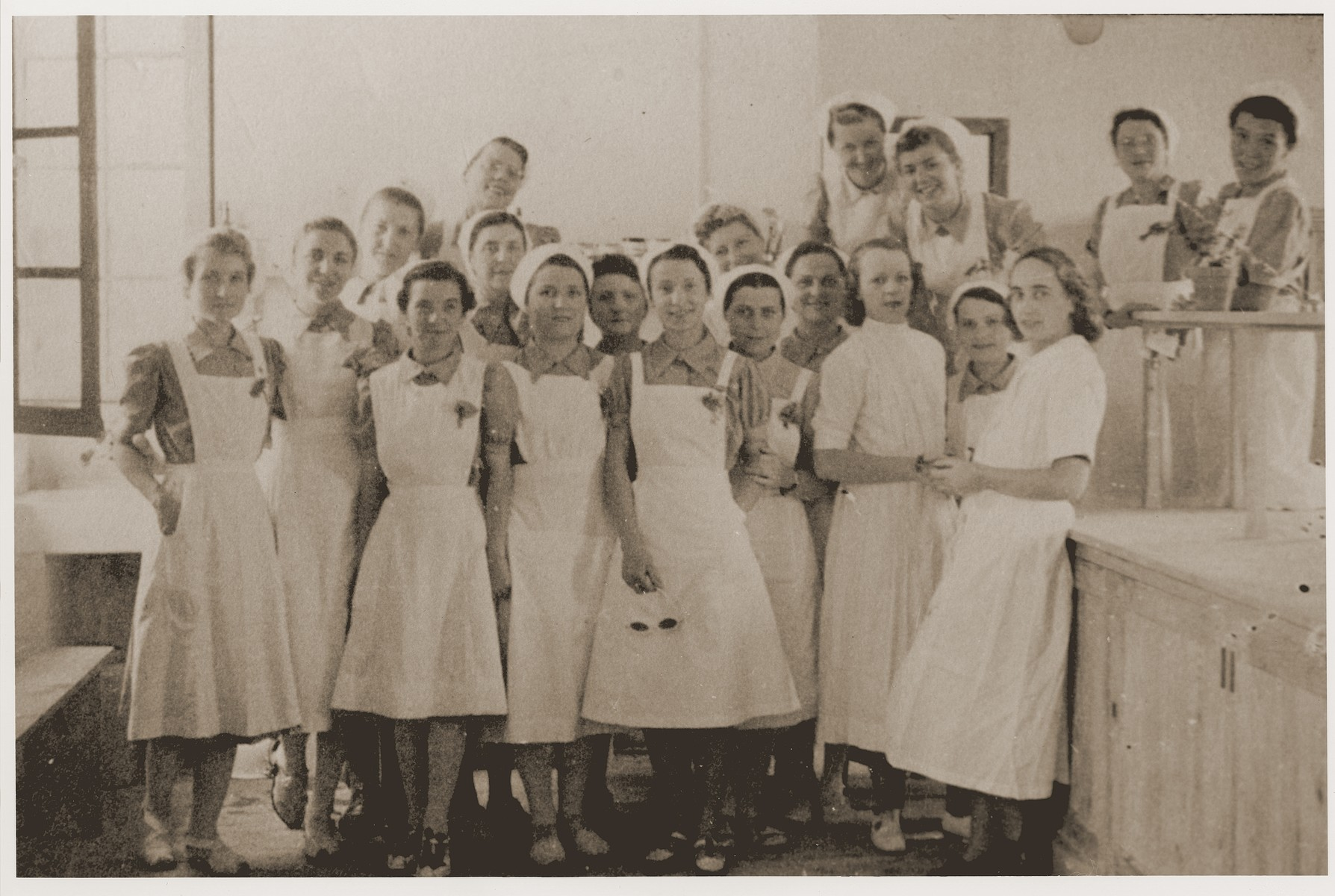 """Nurses in the """"laboratory"""" of the Recebedou camp infirmary.   On the right, leaning against the counter, is Dr. Mirc. Two to the left of her is Mademoiselle Baguelin. At the back on the left, in glasses, is Odette Clauzolles. In the front row, third from the left, is Mademoiselle Rondespierre."""