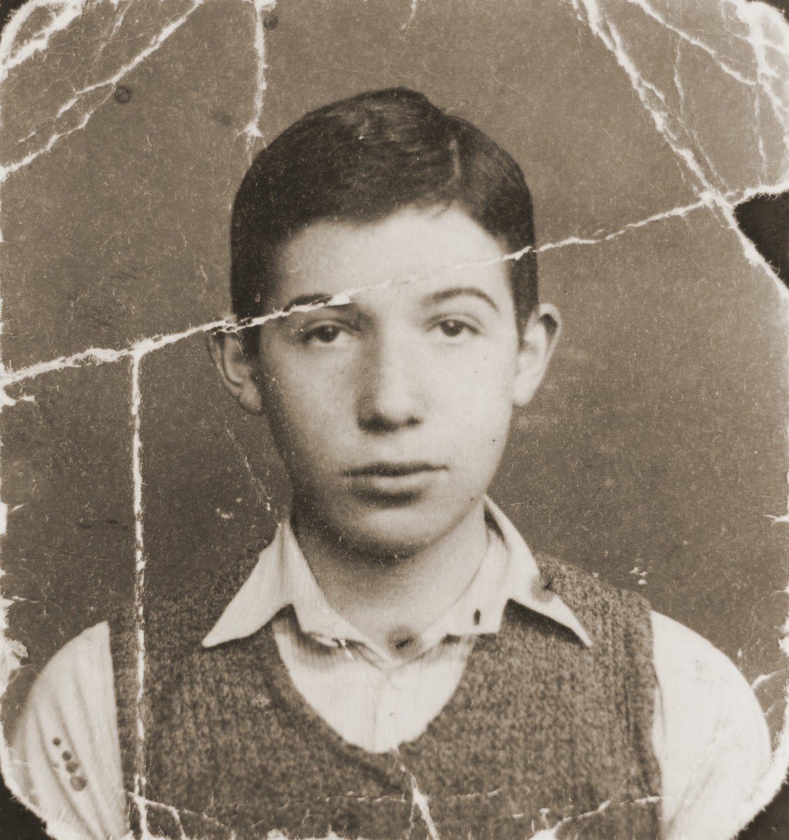 Damaged photograph of Dov Levin, a Jewish school boy in pre-war Kovno, that was preserved through the war by a friend in the sole of her shoe.  Dov Levin gave this photograph to his girlfriend, Rifkale (Rose Kurland), as a keepsake before leaving the Kovno ghetto to join partisans in the Rudninkai Forest.  Rifkale hid the photograph in the sole of her shoe and kept it with her through her deportation from the ghetto and incarceration in the Stutthof concentration camp.  Dov and Rifkale were reunited in 1984 when she returned the photo to him.