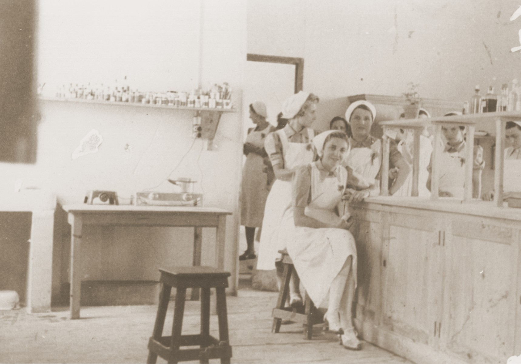"Nurses in the ""laboratory"" of the Recebedou camp infirmary. The woman seated could be Madame Rives. Behind her, in profile, is a nurse who was a delegate of the Red Cross."