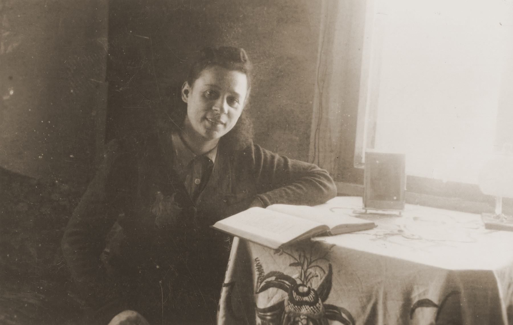 Zoia Bershtanski sits in front of an open book at a table in her room in the Kovno ghetto.  Zoia Bershtanski lived with her married sister, Meri Karnovski, in the ghetto.  Both died in a bunker when the Germans set the ghetto on fire in July 1944.  The photographer, David Ratner, was a friend and a member of the Communist underground.