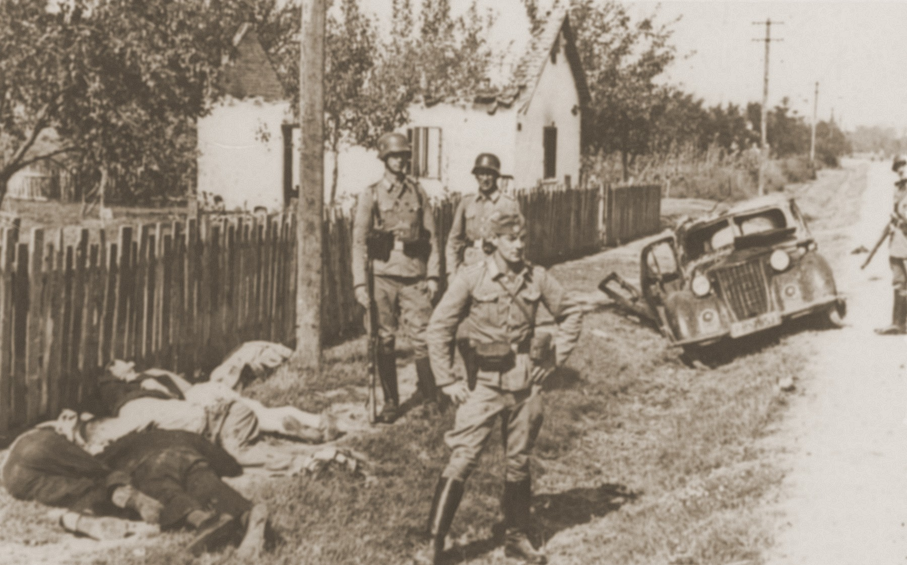 German police stand near the bodies of recently executed Serbian civilians.
