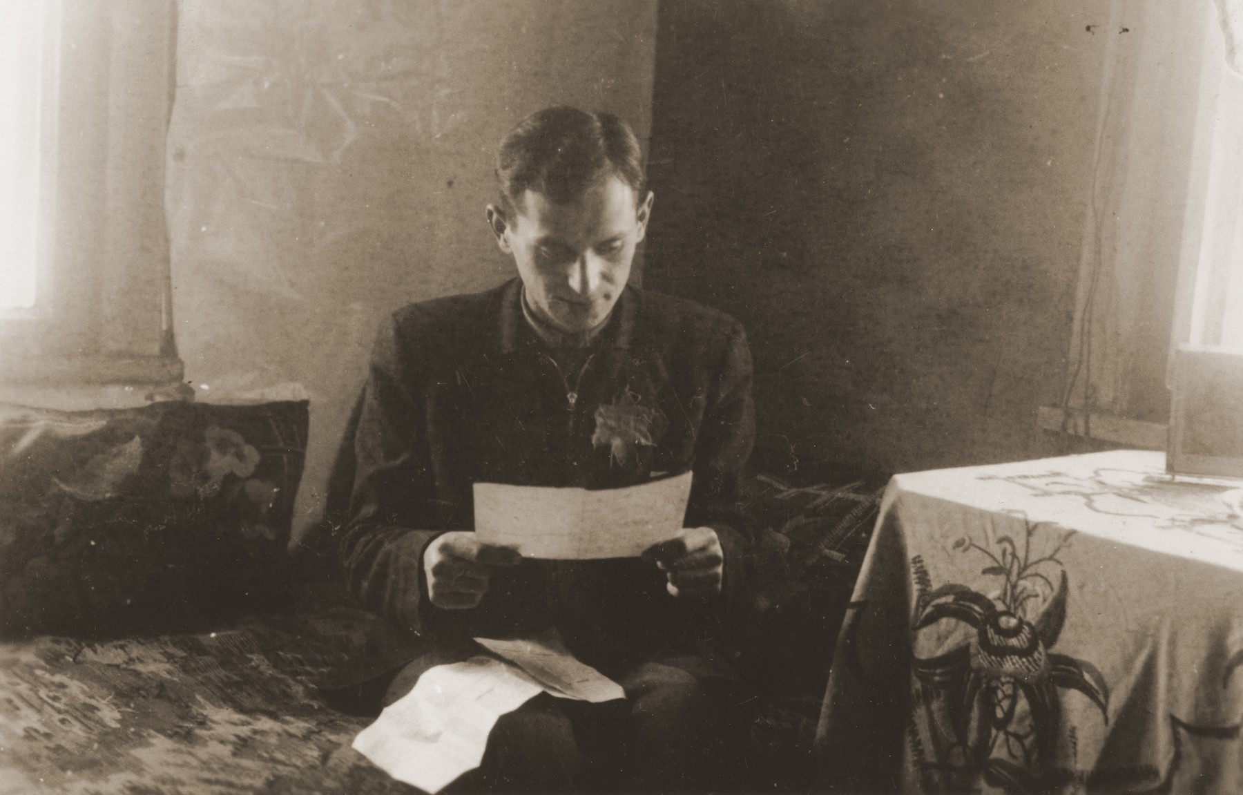 Moshe Musel reads a letter from his wife, Pola, in his room in the Kovno ghetto.  He received this letter one month after Pola escaped to the Aryan side.  Her rescuer, Mikolas Simalis, brought letters back and forth until the ghetto was sealed more tightly in March, 1944.  The photographer, David Ratner, was a friend and a member of the Communist underground.