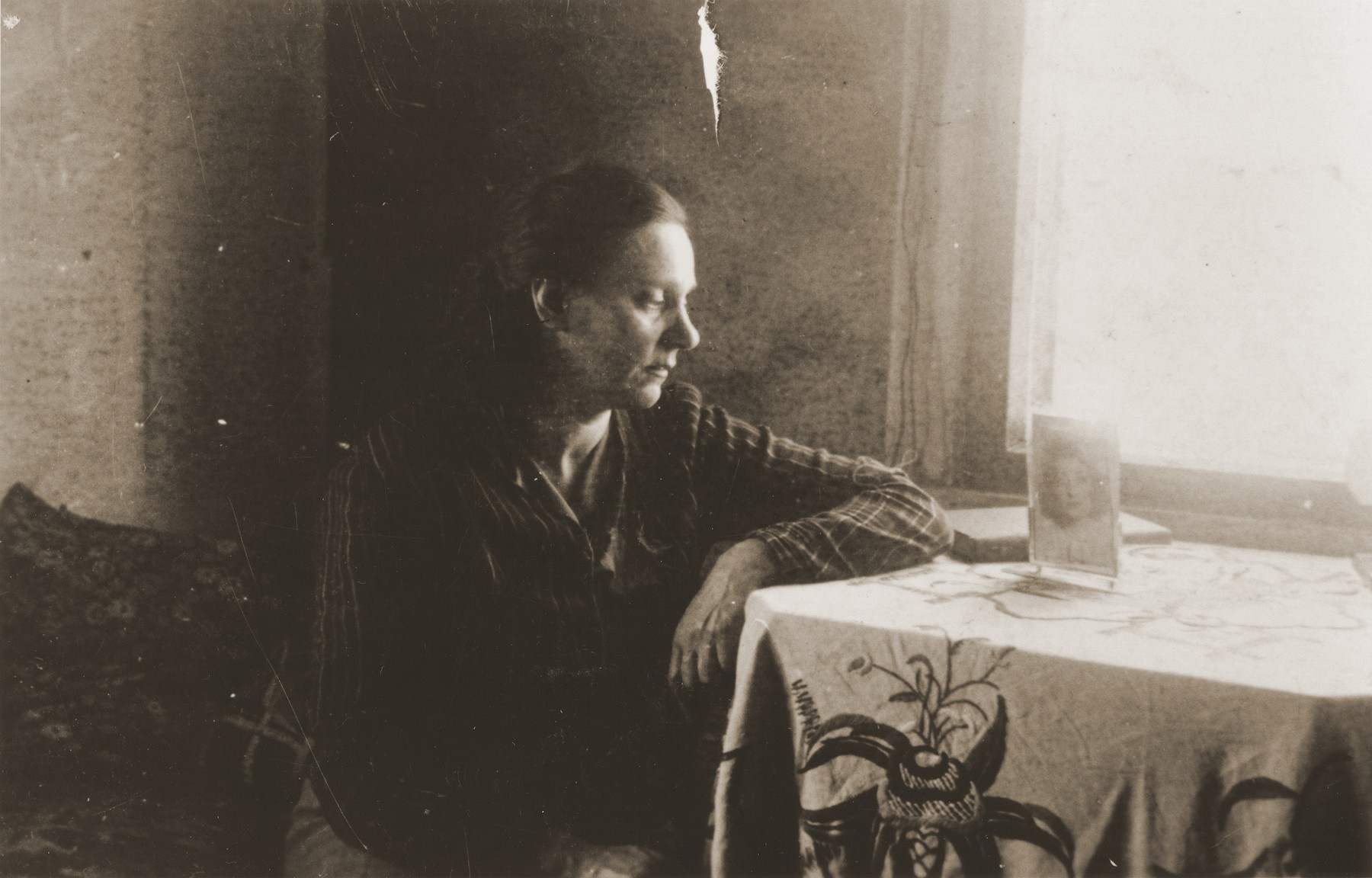 Zoia Bershtanski sits at a table in her room in the Kovno ghetto.  Zoia Bershtanski lived with her married sister, Meri Karnovski, in the ghetto.  Both died in a bunker when the Germans set the ghetto on fire in July 1944.  The photographer, David Ratner, was a friend and a member of the Communist underground.