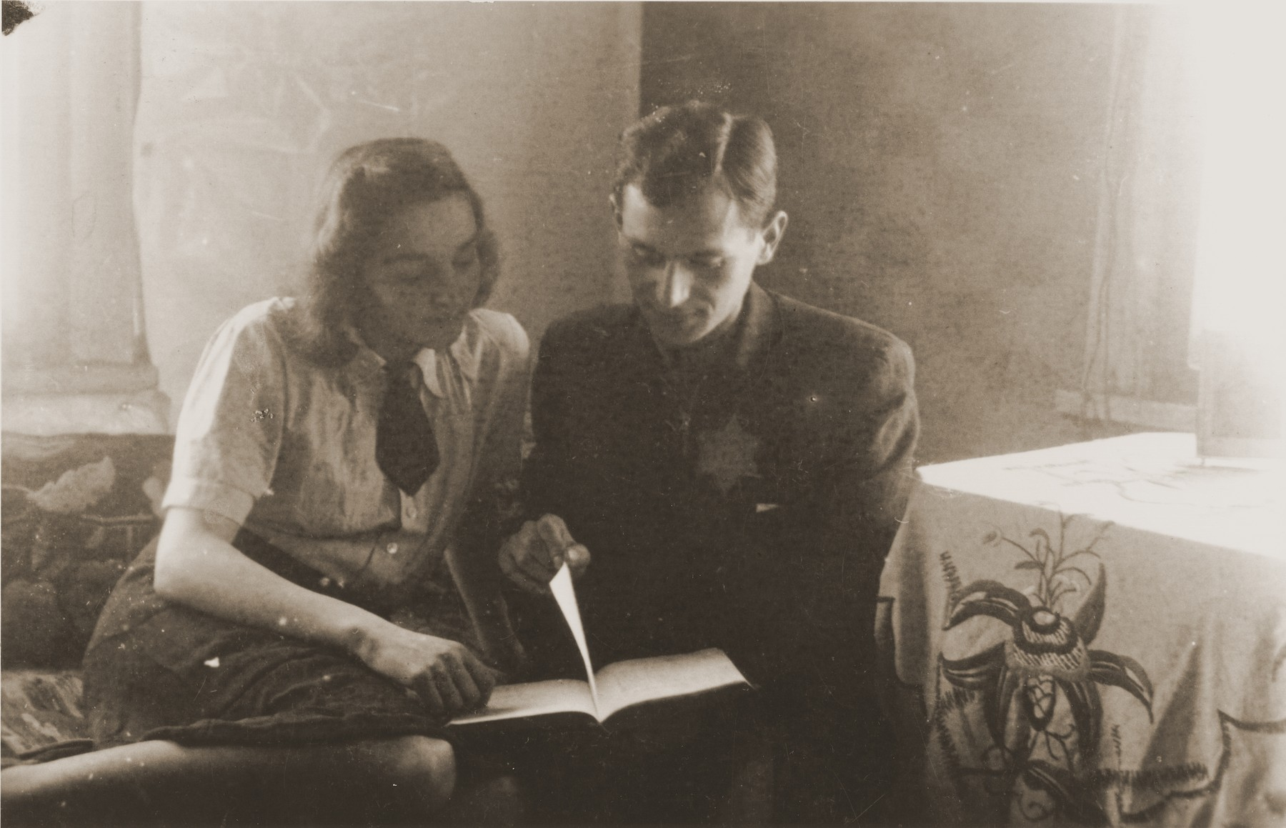 Ida Karnovski and her brother-in-law, Moshe Musel, read a letter from Pola (Karnovski) Musel (Ida's sister and Moshe's wife) in their room in the Kovno ghetto.  They received this letter one month after Pola escaped to the Aryan side.   Her rescuer, Mikolas Simalis, brought letters back and forth until the ghetto was sealed more tightly in March, 1944.  The photographer, David Ratner, was a friend and a member of the Communist underground.