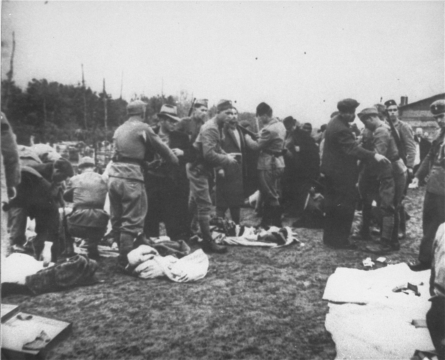 Ustasa guards in the Jasenovac concentration camp strip newly arrived prisoners of their personal possessions.  Andor Willer is pictured in the left foreground (left) in the light colored hat and dark overcoat being manhandled.  Mr. Willer perished in Jasenovac on December 25, 1944, along with his parents, brothers, and sisters.