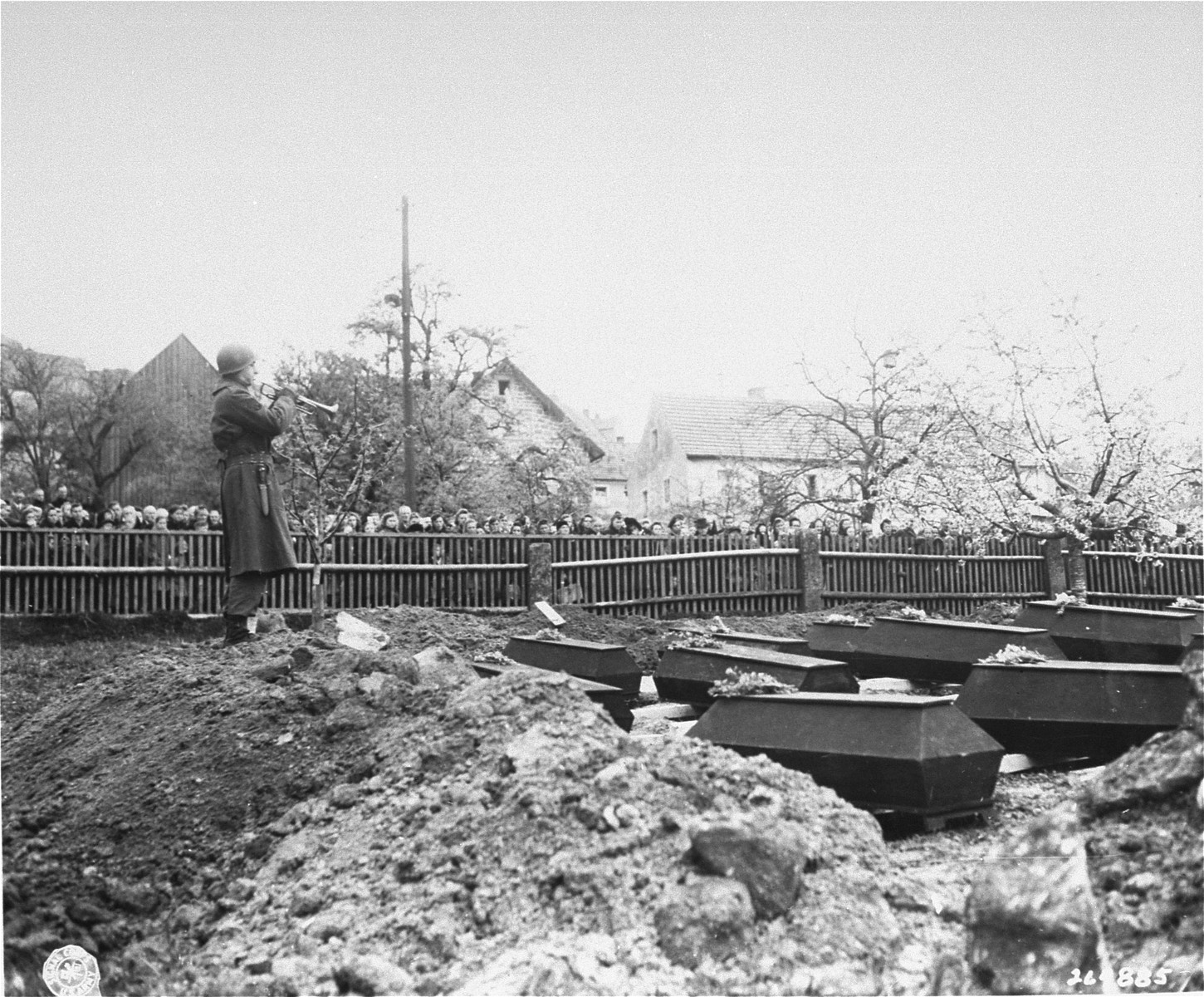 Tec Sgt. 4 James F. Flaha, of the 97th Infantry Division band, blows taps over the graves of prisoners murdered in the Flossenbuerg concentration camp.    Residents of town of Flossenbuerg have been forced to witness the burial.