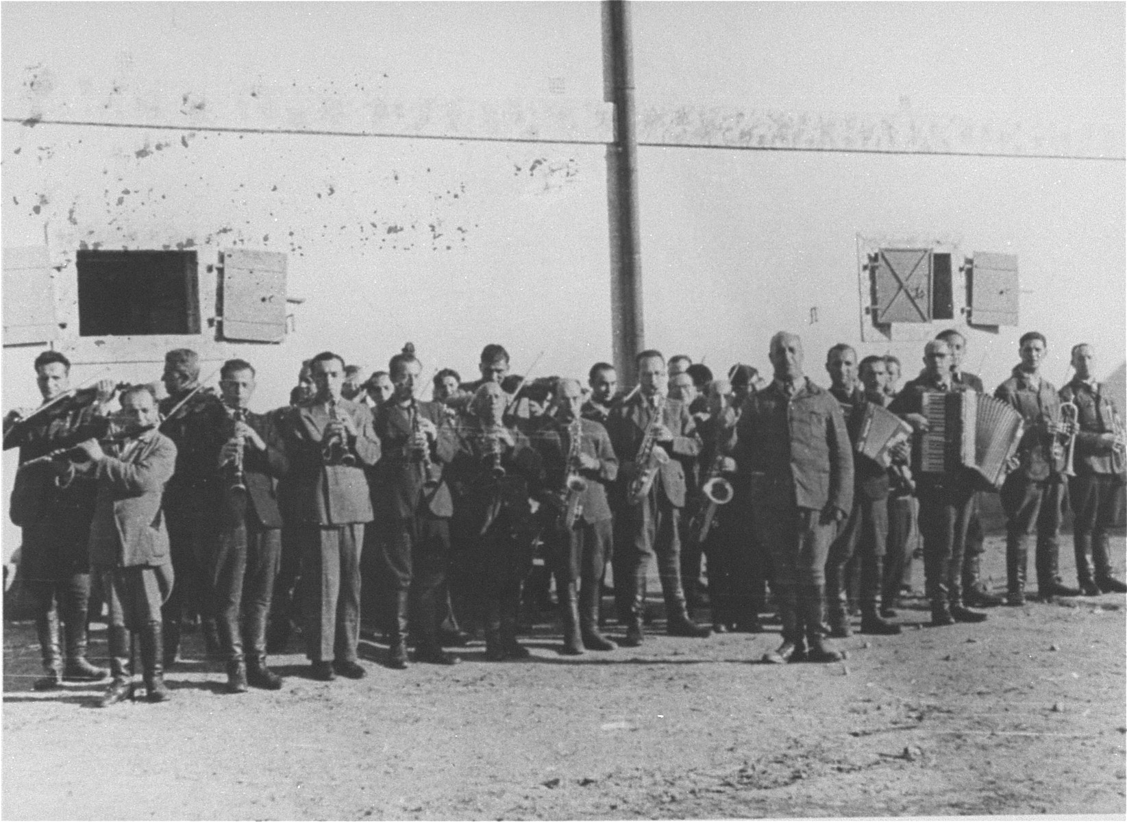 "Members of the camp orchestra perform in front of a barracks in the Janowska concentration camp.  The Janowska orchestra included some of the leading Jewish musicians in Lvov, among them violinist Leonid Stricks and cellist Leon Eber.  The SS forced the orchestra to perform during selections and actions and even ""commissioned"" a special composition to be played on these occasions.  Entitled ""Todestango"" [Tango of Death], the piece was composed by Yakub Munt (sp?), former director of the Lvov opera.  The music was based on an earlier work by Eduardo Bianco.  The members of the orchestra met their end in 1943 when they were shot to death by their overseers while playing their instruments."