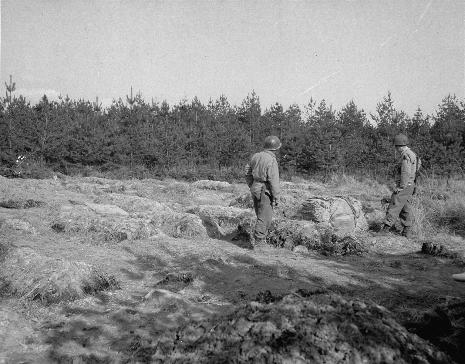 Two U.S. soldiers with the 9th Armored Division stand in the middle of a field of graves, near the Flossenbuerg concentration camp.