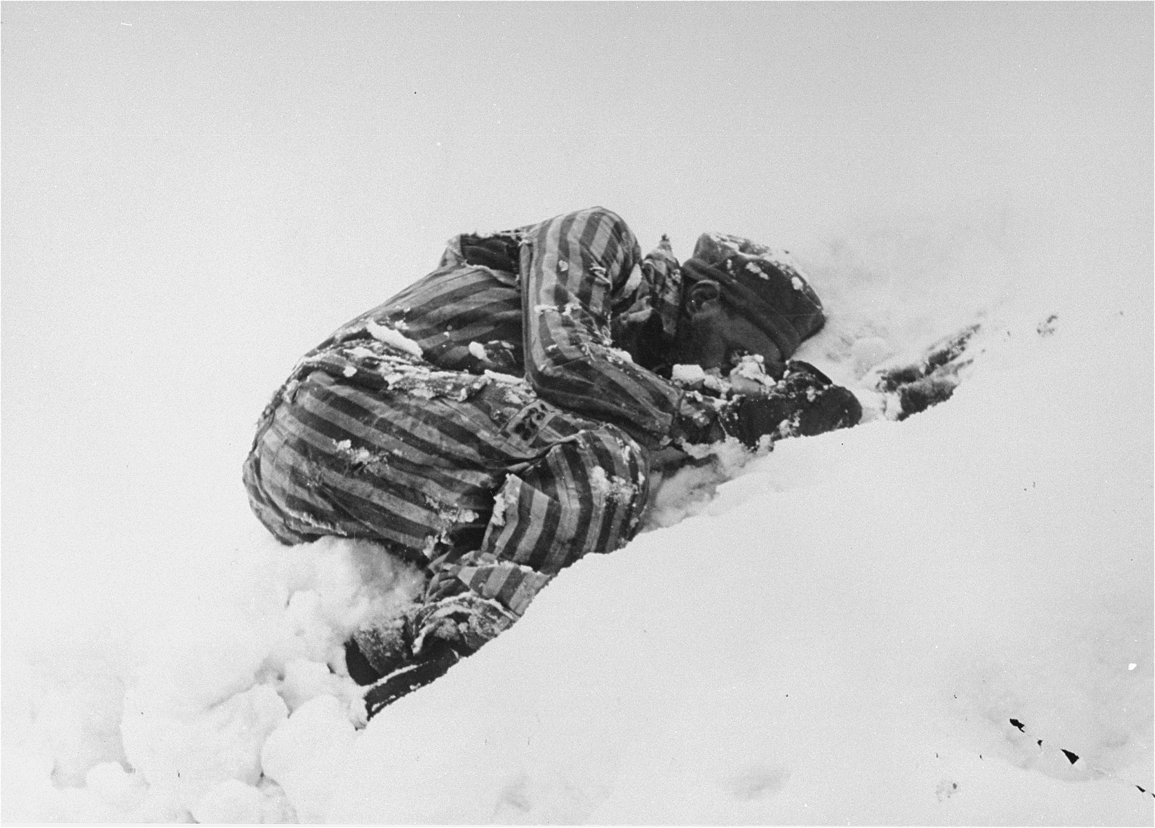The frozen body of a Jewish prisoner who was beaten to death by the SS lies in the snow.