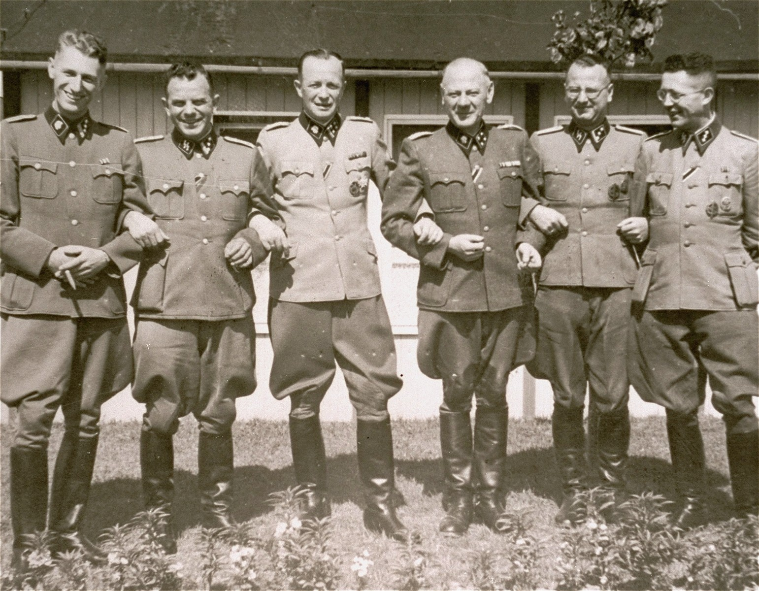 """Commandant Franz Ziereis poses with members of the SS staff of the Mauthausen concentration camp.  From left to right are Haupsturmfuehrer Erich Wasitzky (the camp apothecary);  Karl Schulz, chief of """"Politischer Abteilung"""" (Gestapo office in the camp); Standartenfuhrenfuehrer Franz Ziereis (the camp commandant); Sturmbannfuehrer Eduard Krebsbach (camp doctor); Karl Boehmichen (camp doctor) and an unidentified Obersturmfuehrer."""