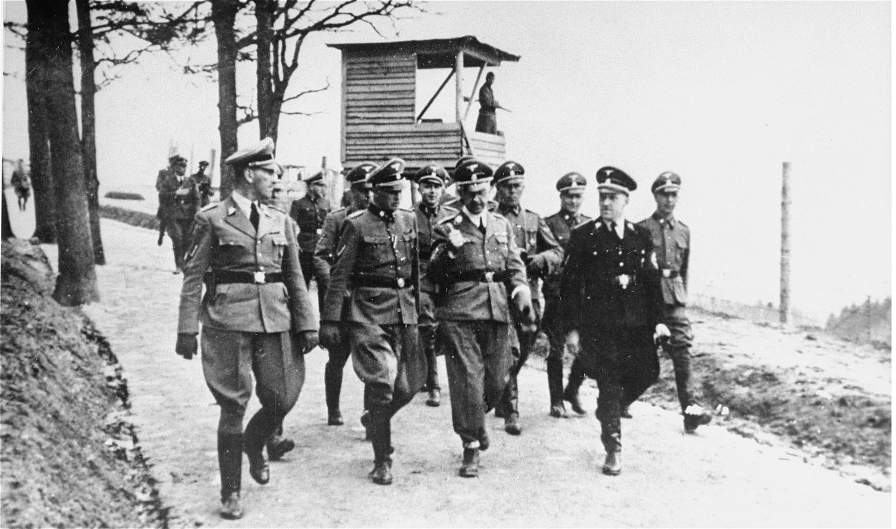 High ranking SS officials on an inspection tour of the Mauthausen concentration camp.    Pictured in the front row from left to right are Ernst Kaltenbrunner, Franz Ziereis, Heinrich Himmler, Karl Chmielewski, and  August Eigruber.  At the far right in the second row is George Bachmayer.