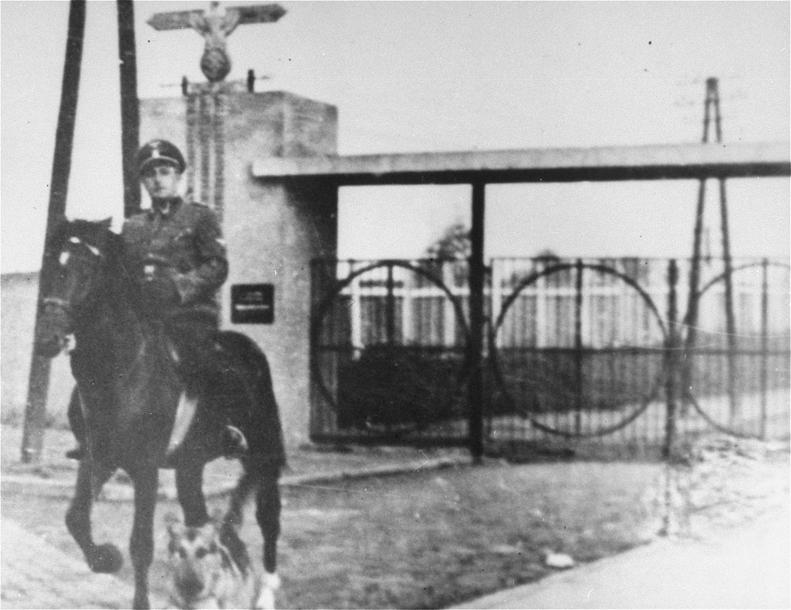 SS Untersturmfuehrer Gustav Wilhaus rides a horse out the main gate of the Janowska concentration camp.