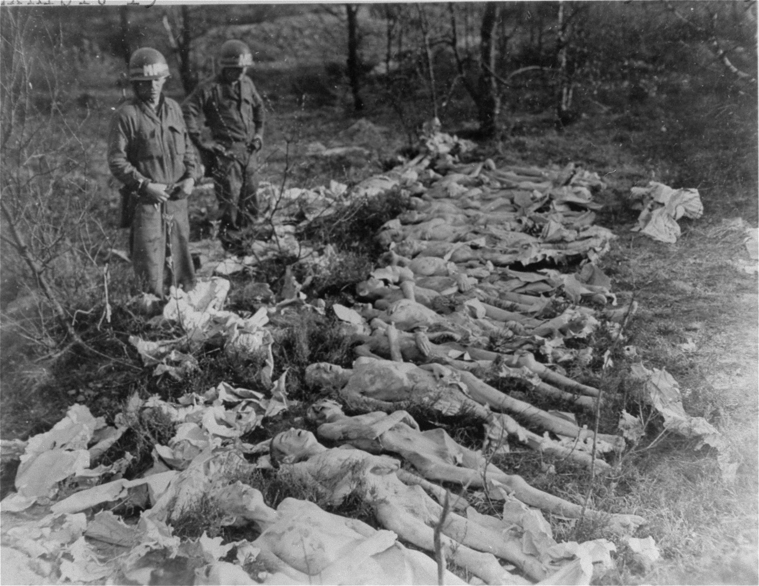 Two American soldiers stand among the bodies of female prisoners exhumed from a mass grave near the Helmbrechts concentration camp, a sub-camp of Flossenbuerg.