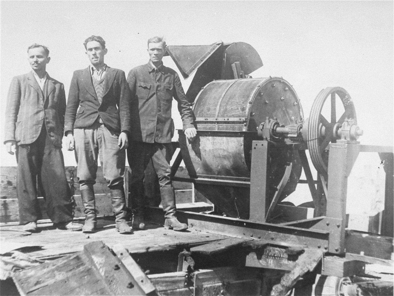 Jewish prisoners forced to work for a Sonderkommando 1005 unit pose next to a bone crushing machine in the Janowska concentration camp.  Pictured from left to right are: unknown, David Manusevitz, and Moses Korn.  This photograph ws taken soon after liberation for the Extraordinary Commission or the Red Army.