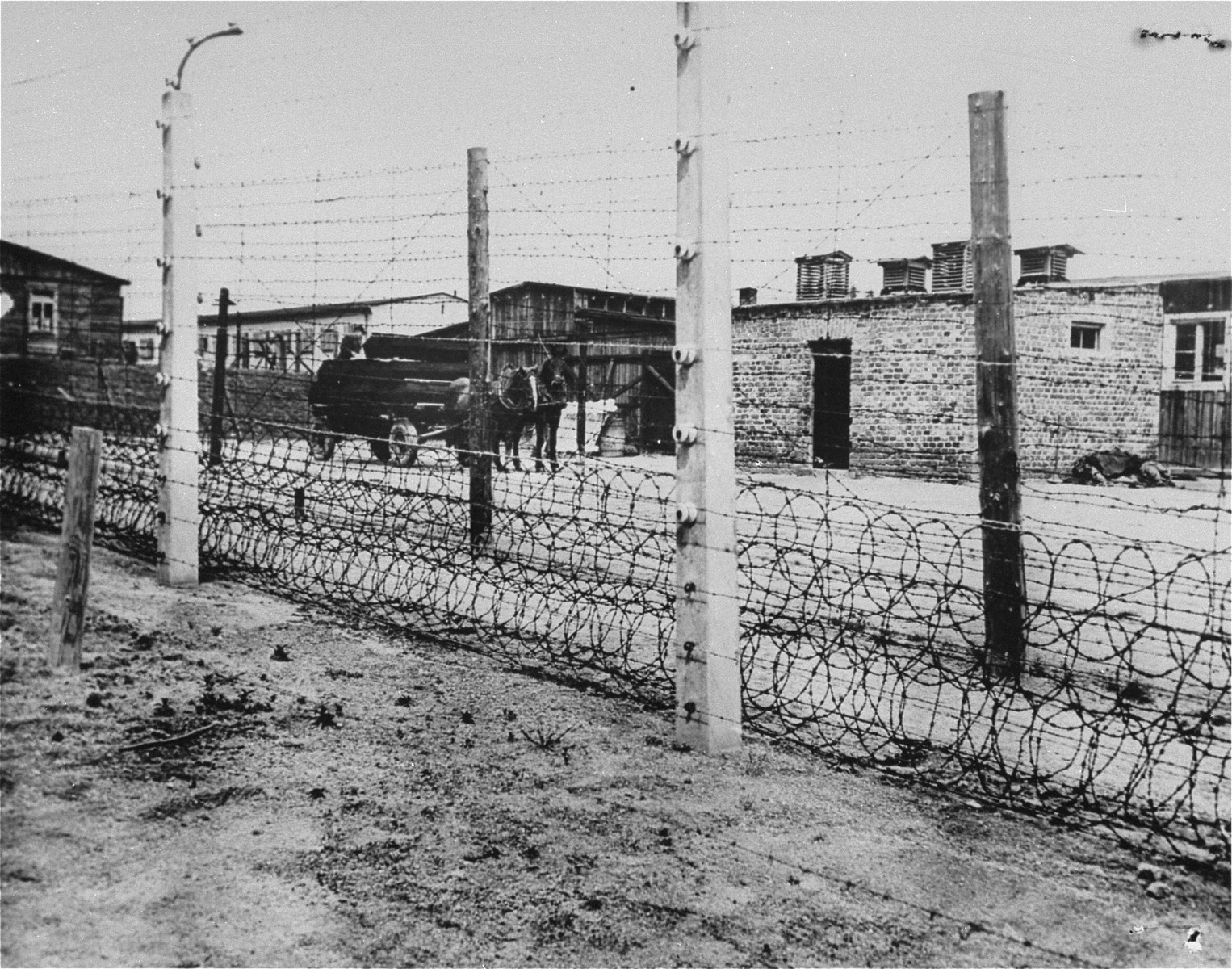 A section of the barbed wire fence and barracks in the Flossenbuerg concentration camp.