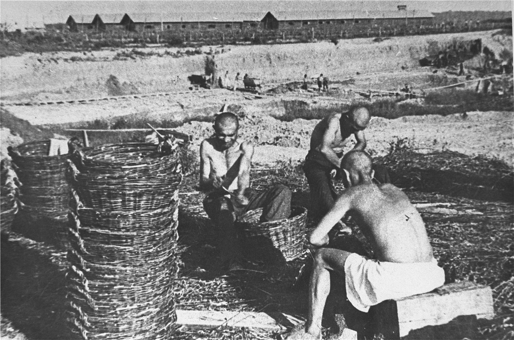 Prisoners at forced labor weaving baskets [possibly at one of the Jasenovac concentration camps].