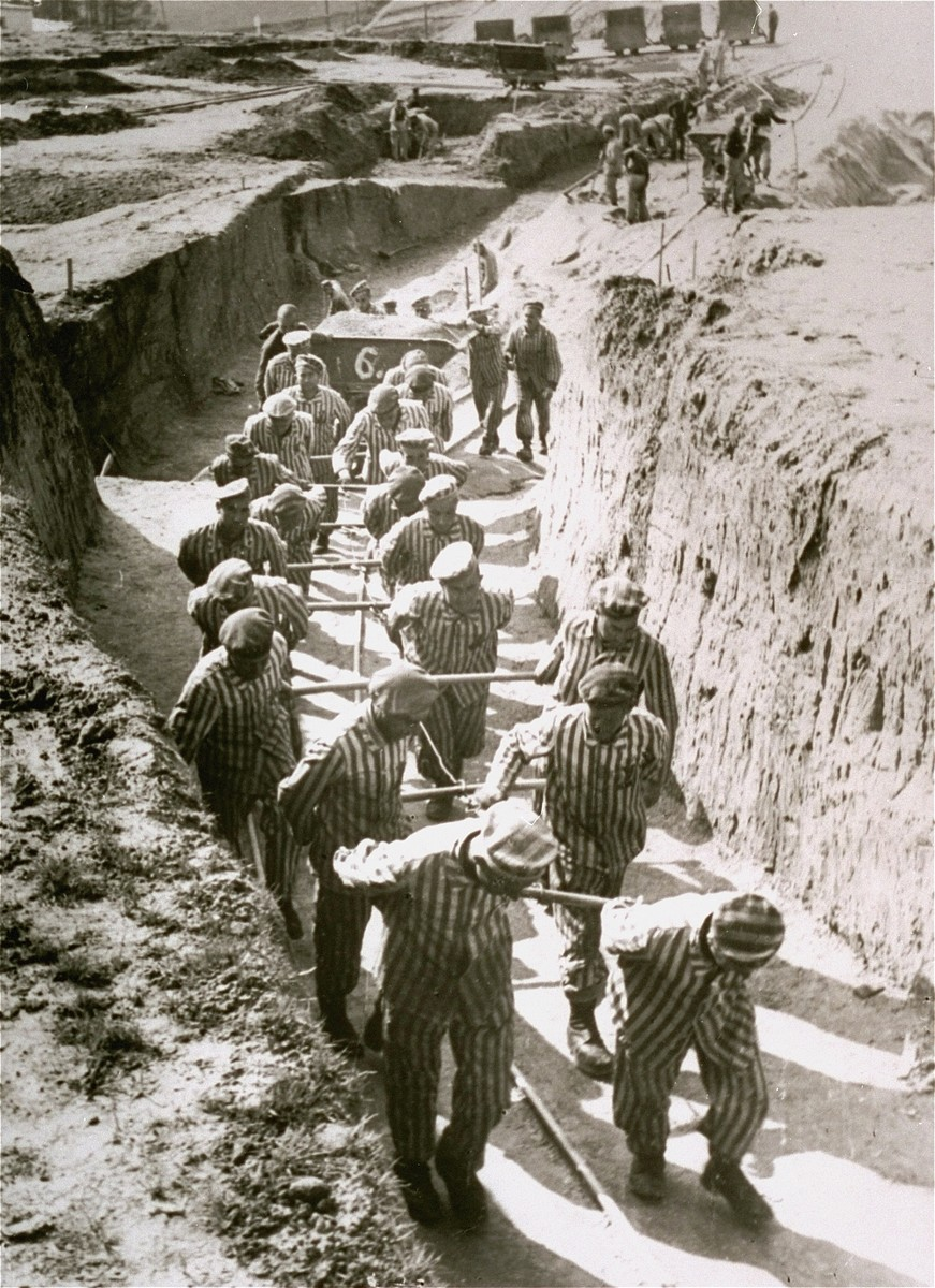 """Concentration camp inmates at forced labor hauling cartloads of earth for the construction of the """"Russian camp""""."""
