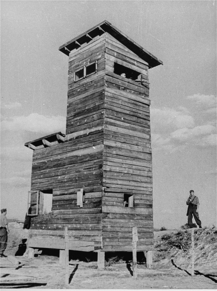An Ustasa guard stands next to a watch tower in the Jasenovac concentration camp.