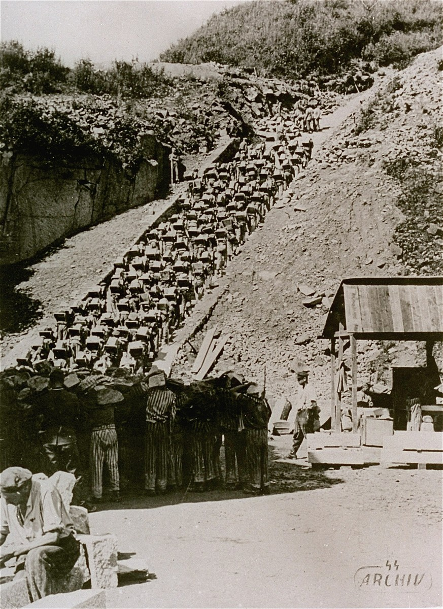 "Prisoners carry large stones up the ""stairs of death"" (Todesstiege) from the Wiener Graben quarry at the Mauthausen concentration camp."
